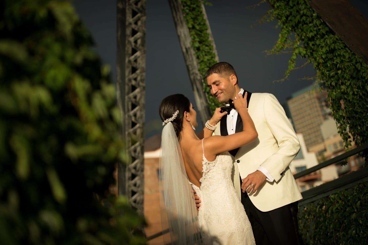 Marika adjusts Dean's bowtie on the Wynkoop Street Bridge during their wedding portraits in Denver.