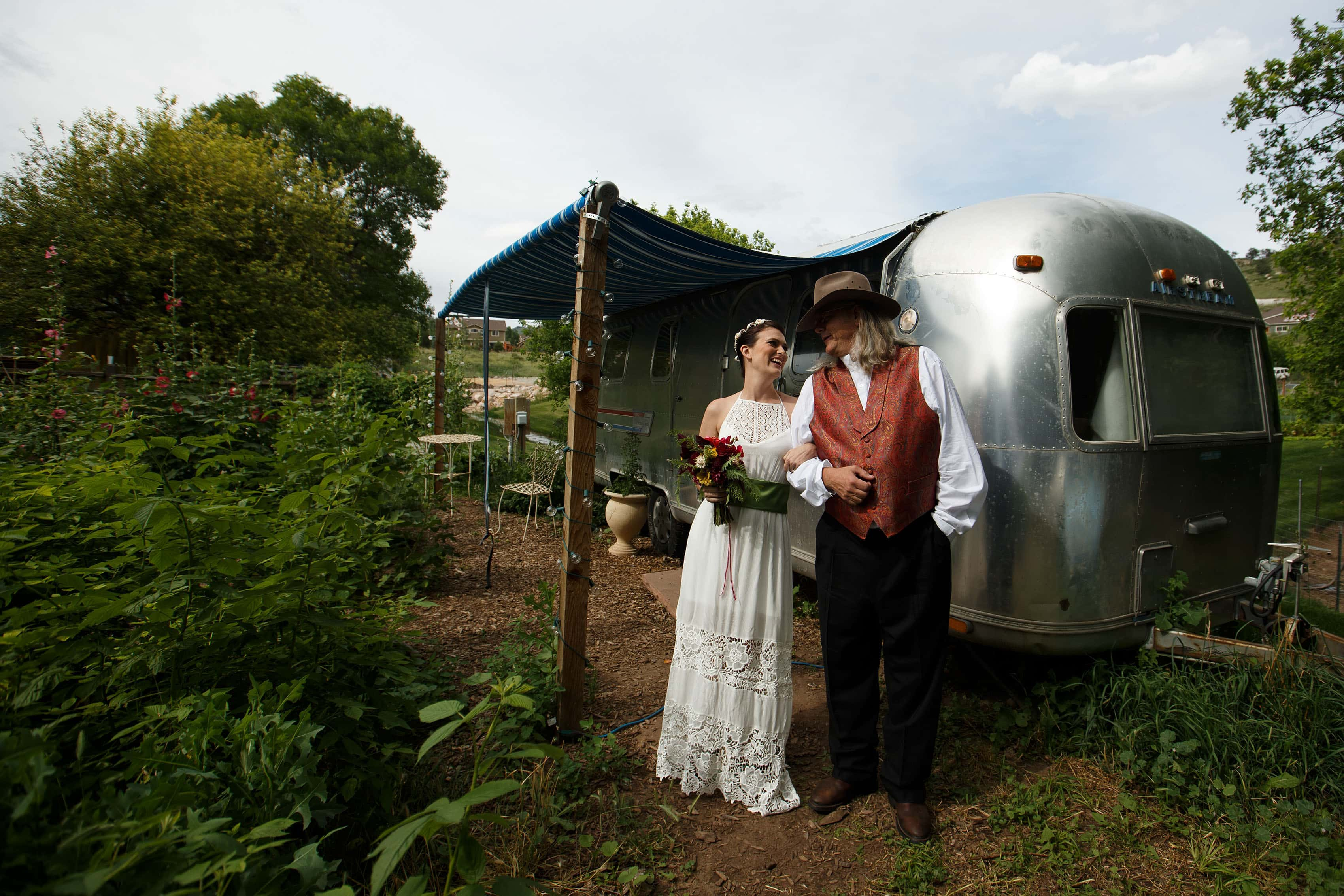 Bride and her father stand outside the airstream during her Lyons Farmette wedding