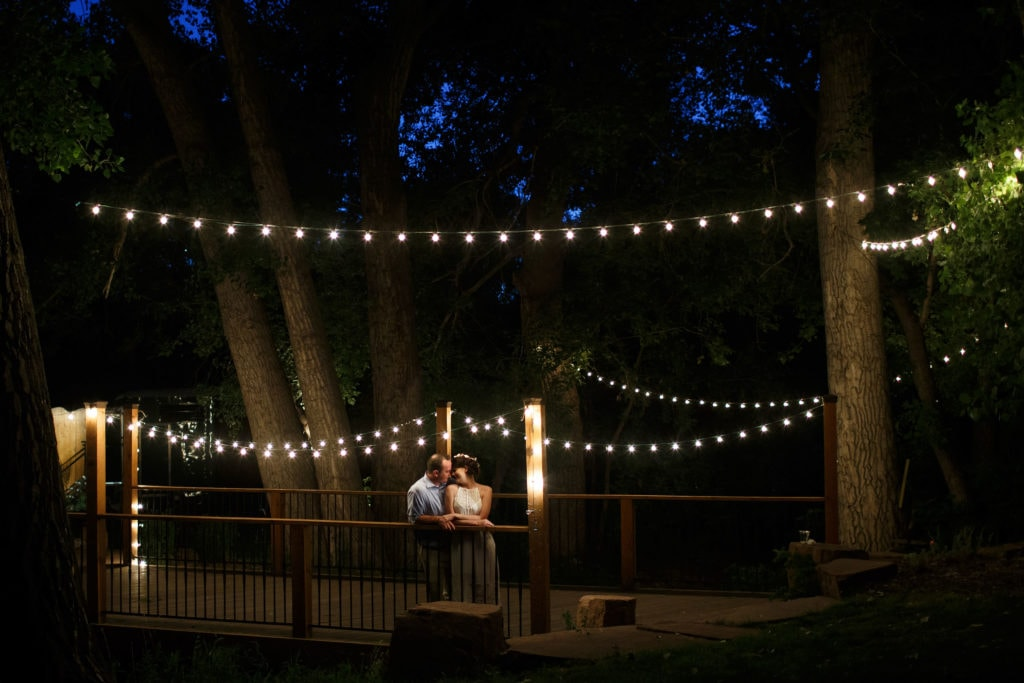 Couple embraces at twilight under market lights during their Lyons Farmette wedding