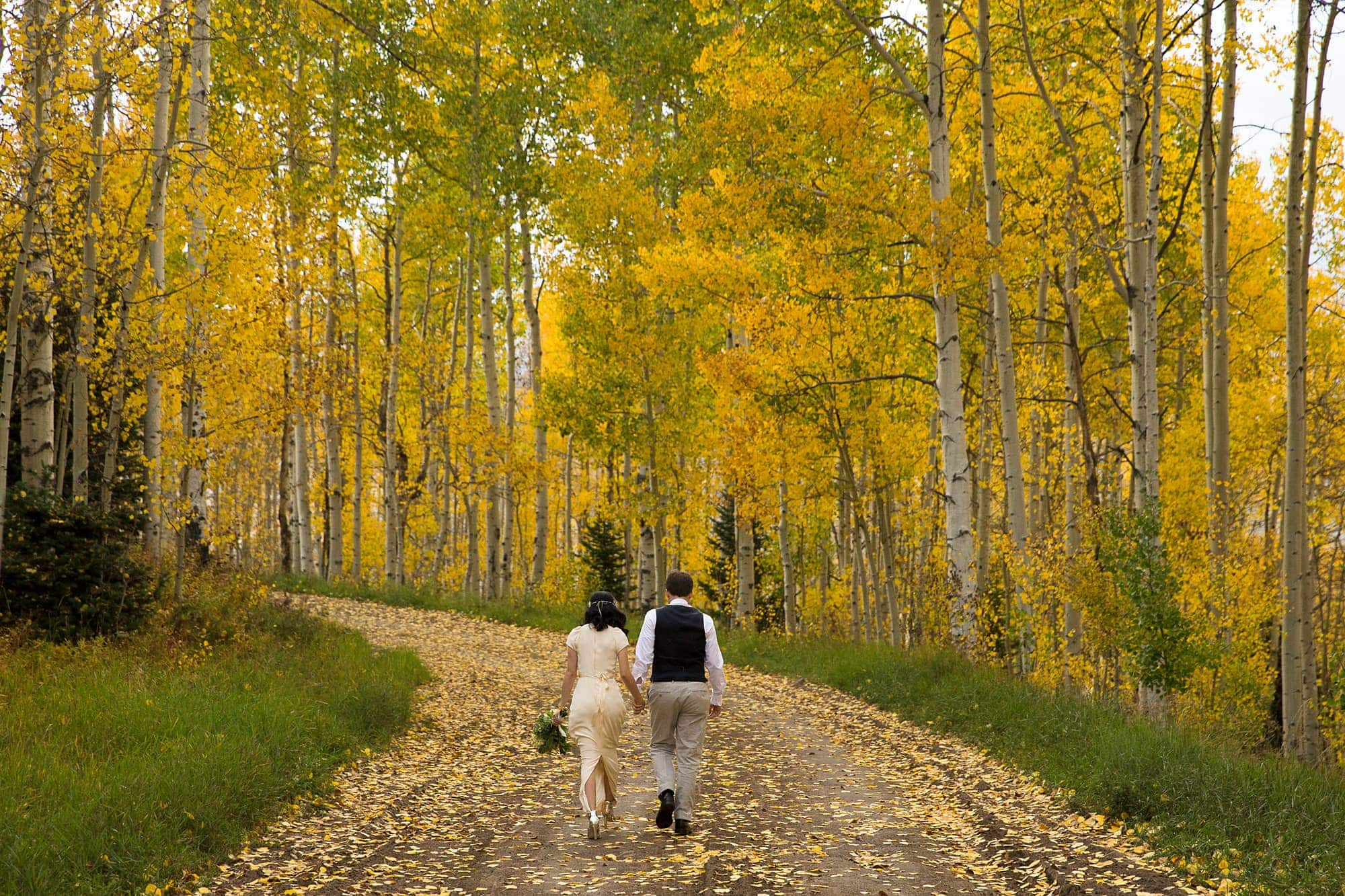 Allison and Walker walk down a road covered in yellow aspen leaves after their Lynn Britt Cabin wedding in Snowmass Village near Aspen, Colorado.