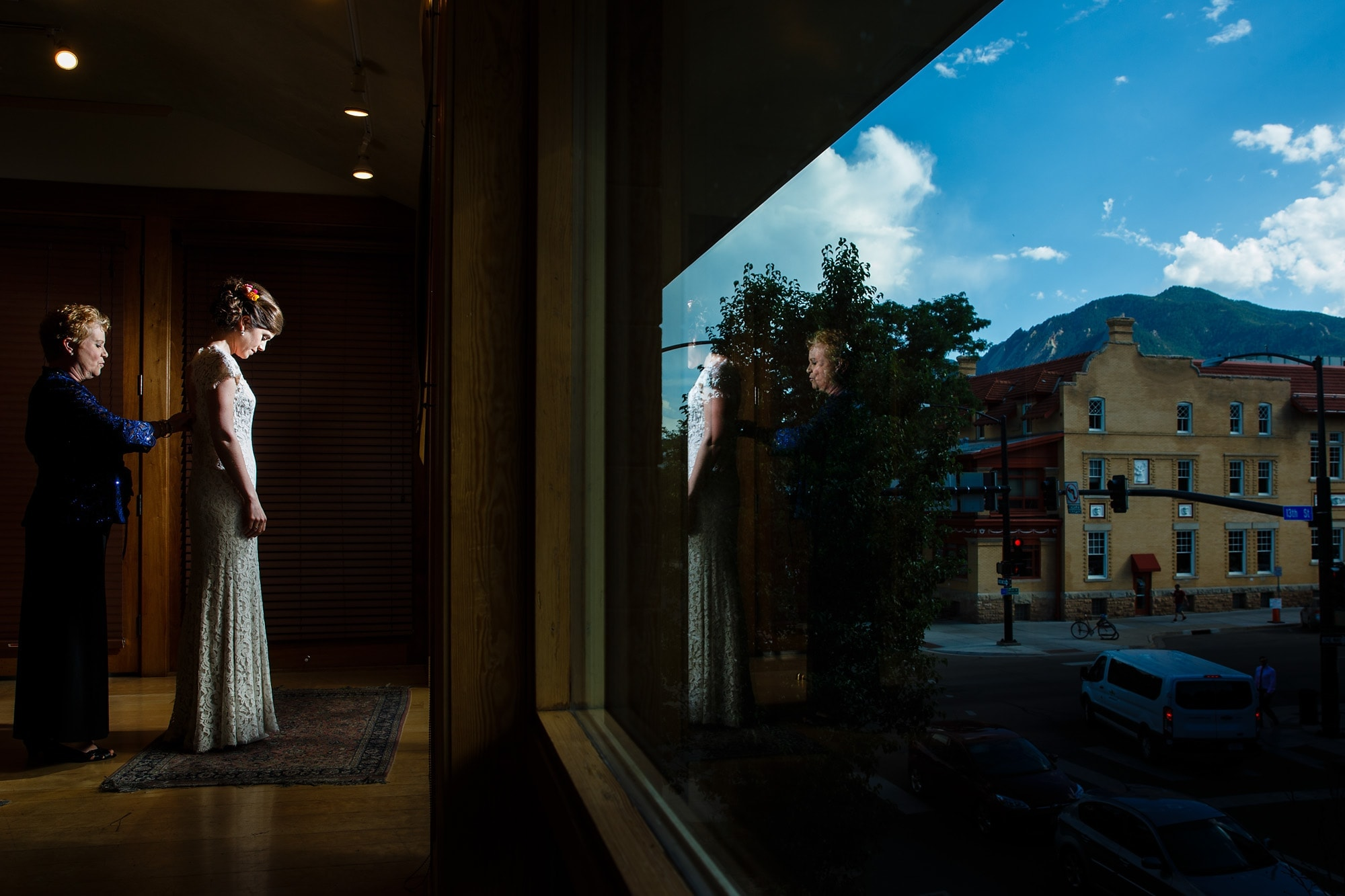 The flatirons emerge over Boulder while the bride and her mother adjust her dress