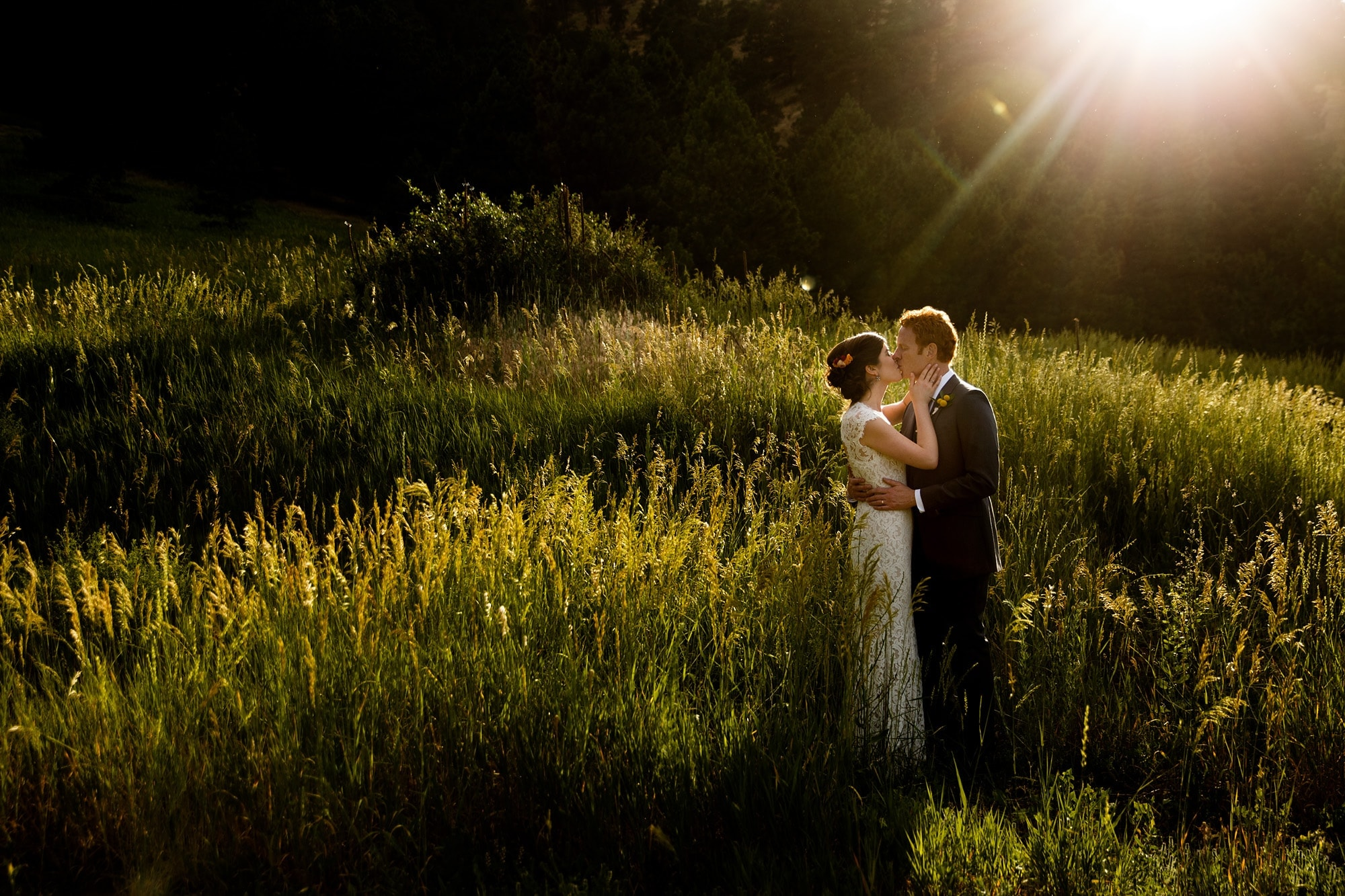 The sun flares over the couple as they kiss in Boulder near Centennial trailhead