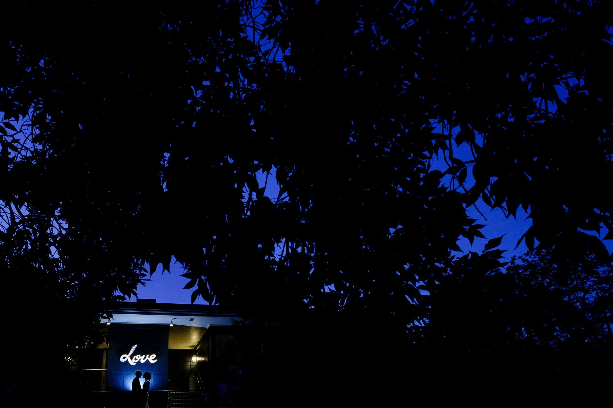 The couple shares a moment together outside of Rembrandt Yard in Boulder during twilight