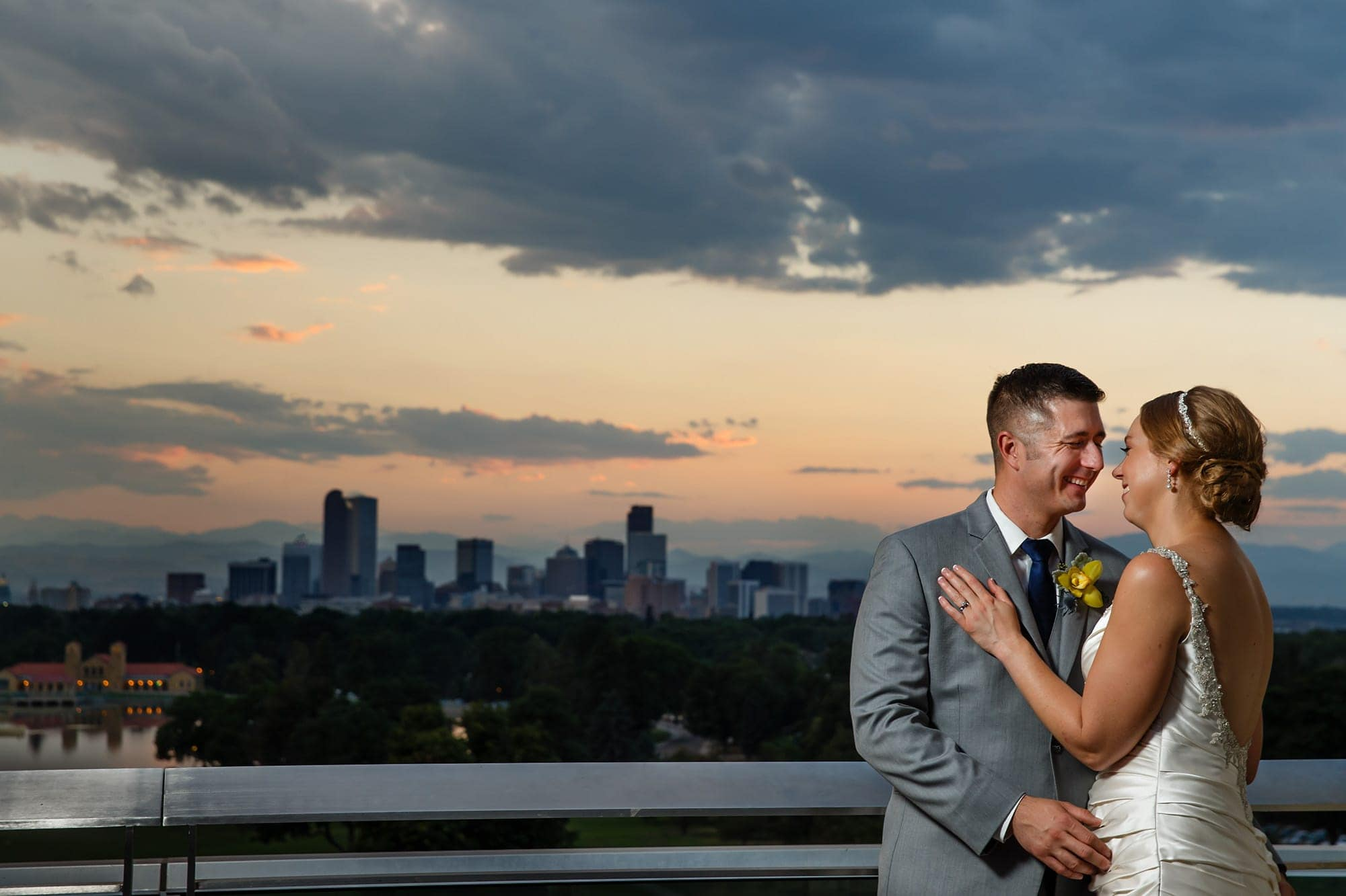 The couple pose for a portrait with the Denver skyline and City Park behind them after their wedding ceremony