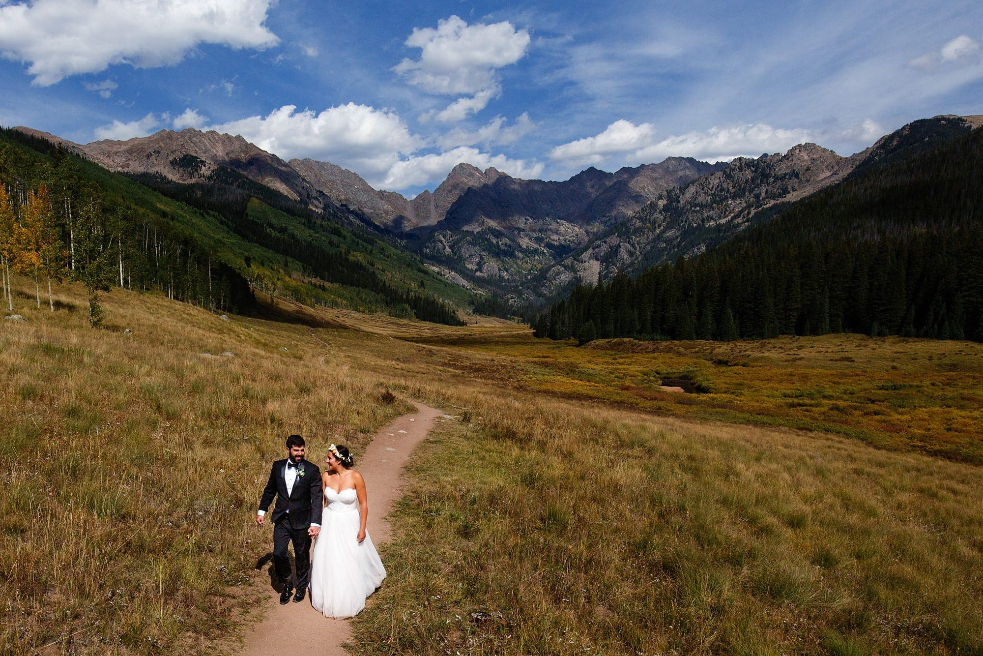 The bride and groom walk along the hiking path at Piney River Ranch with the Gore mountain range in the background near Vail, Colorado.