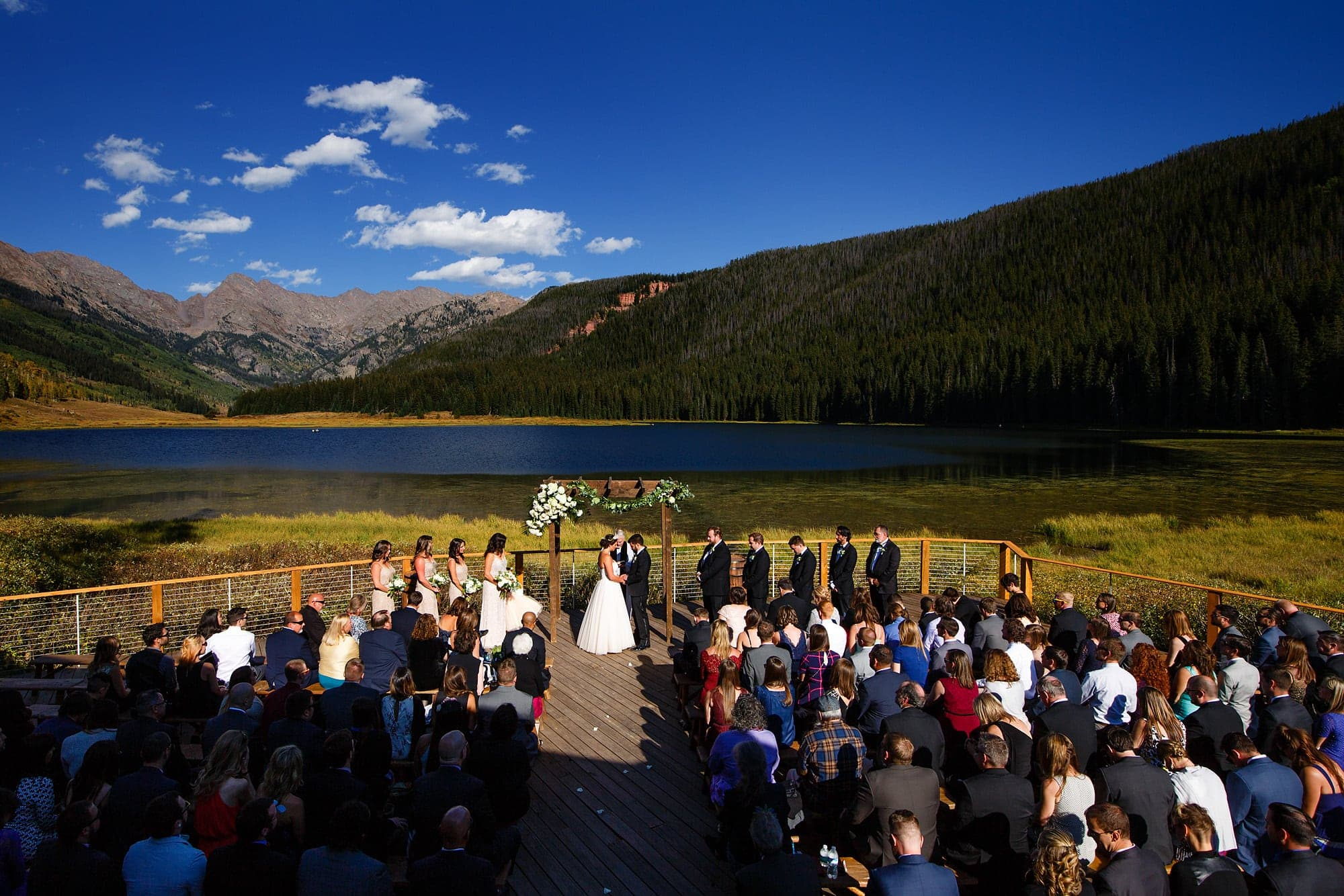 The wedding ceremony takes place on the deck at Piney River Ranch in September 2016 outside of Vail, Colorado with the Gore mountain range in the background.