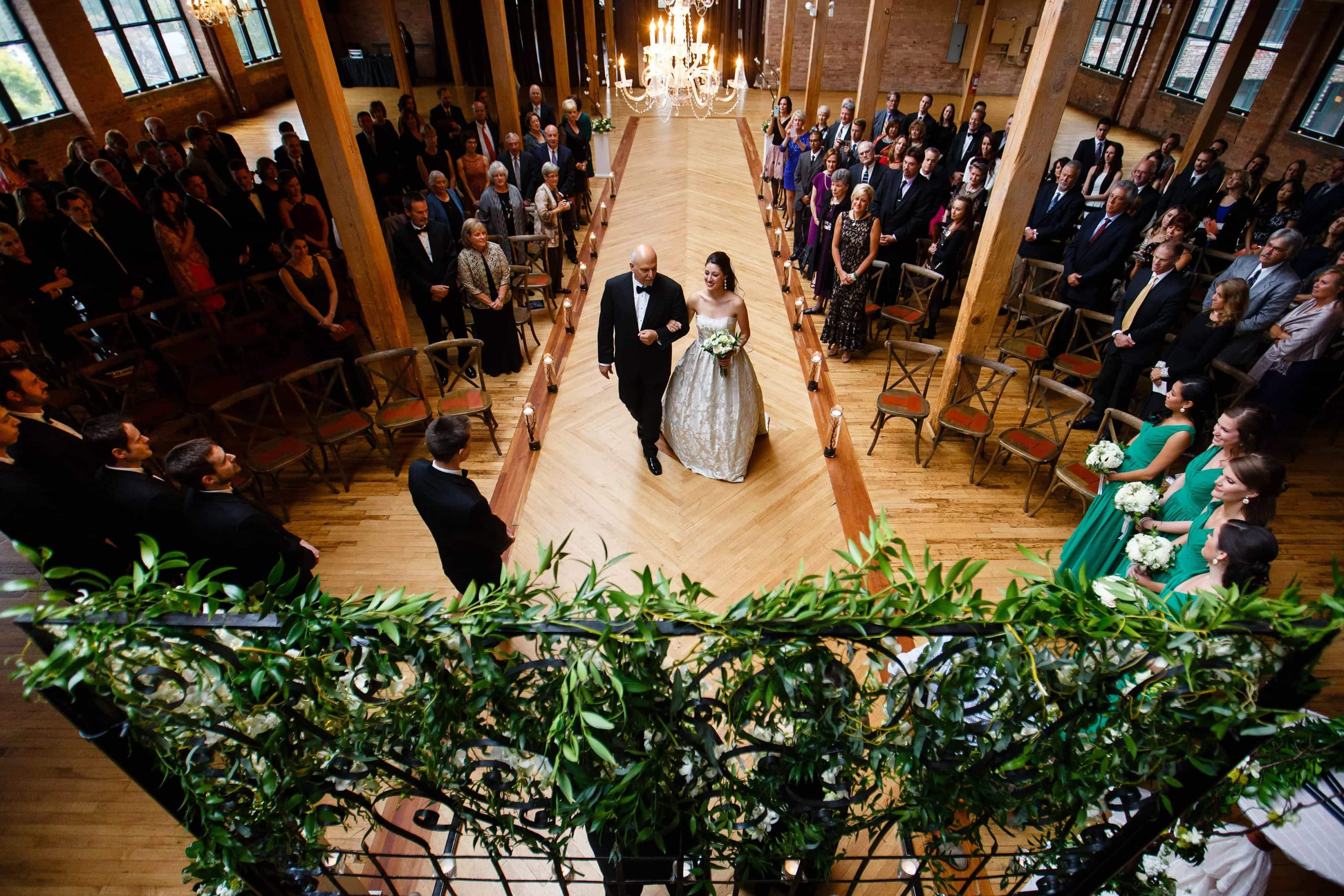 A father walks his daughter down the aisle during her wedding at Bridgeport Art Center in Chicago, Illinois.