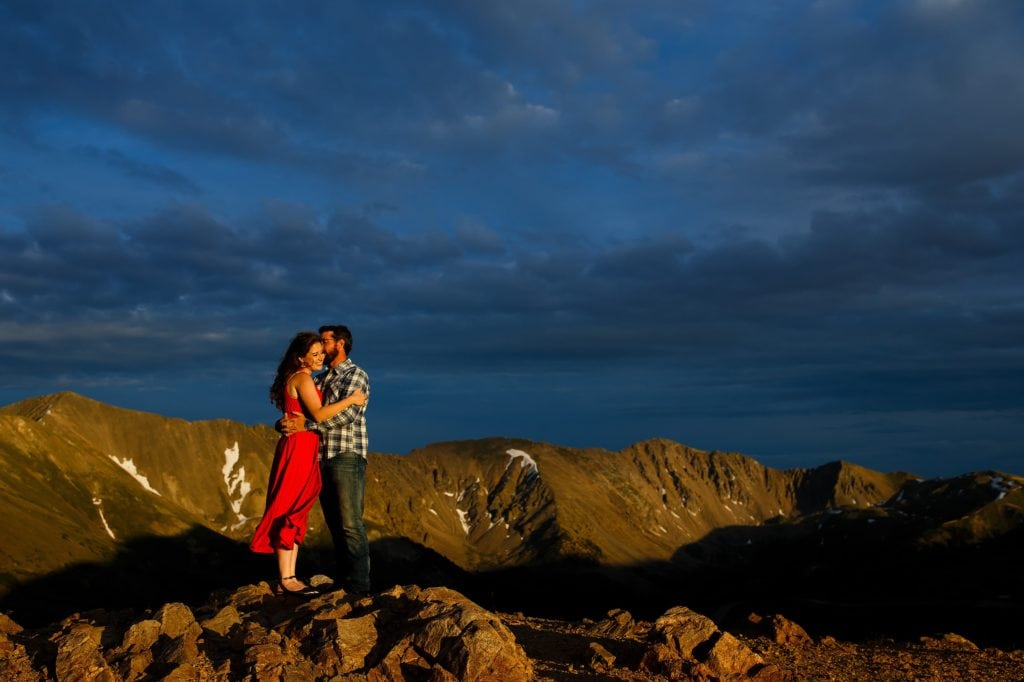 Daniel kisses Mallory as the two embrace on top of Loveland pass as the sun sets near Keystone Colorado