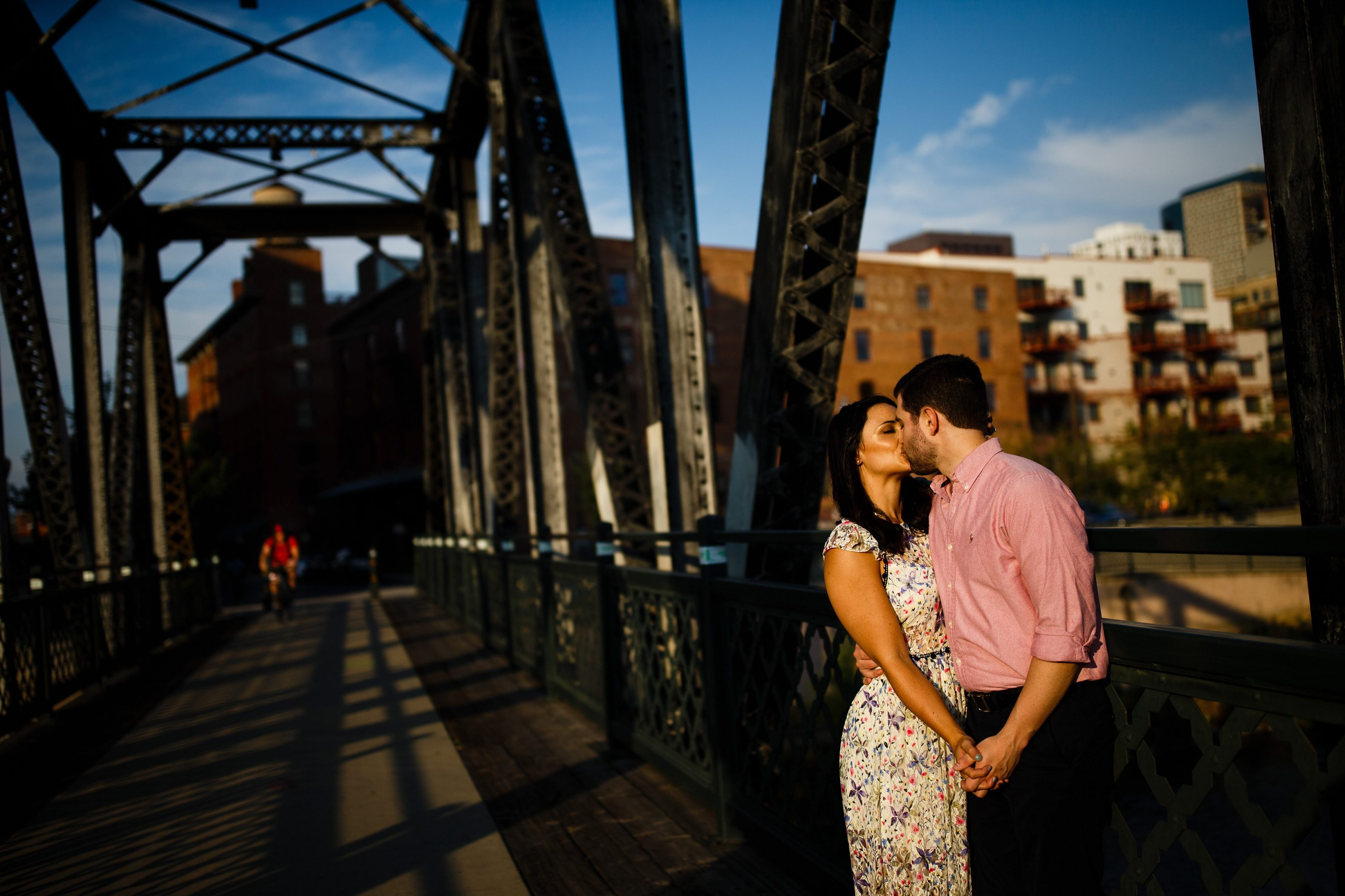 Jordan and Danielle kiss on the Wynkoop bridge during their downtown Denver engagement session in the LoDo neighborhood in August
