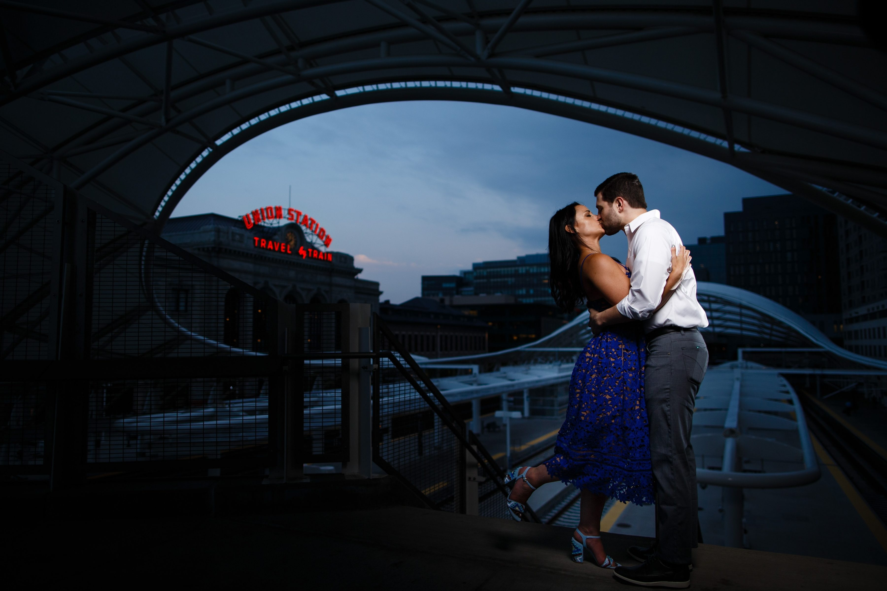 Danielle and Jordan share a kiss on the platform outside Union Station during their engagement photos in lower downtown Denver