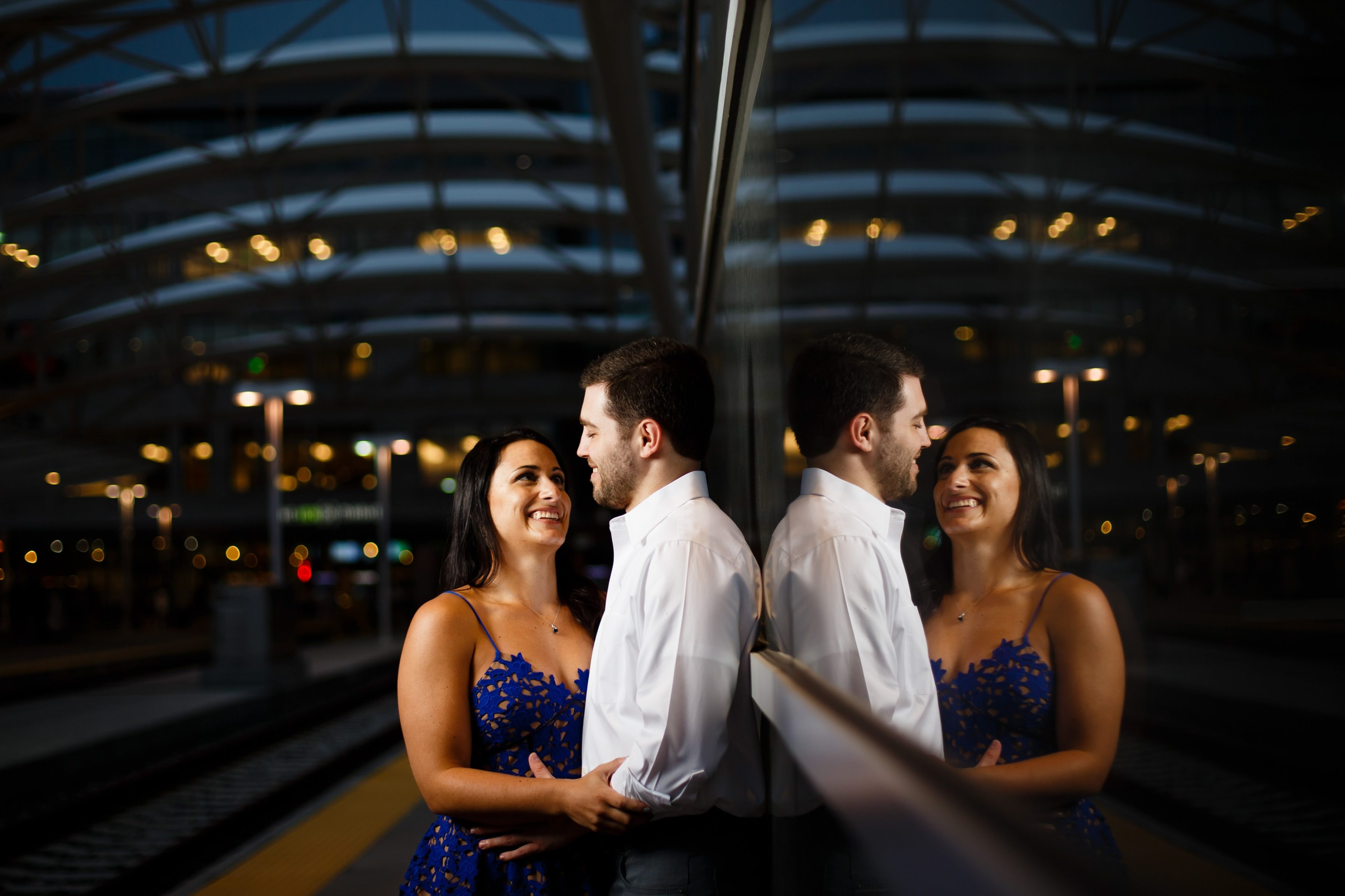 Danielle and Jordan embrace each other on the platform at Union Station in Denver, Colorado for their engagement photos
