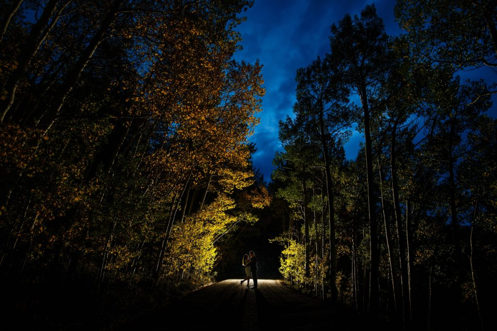 Shabnam and Joseph embrace on Boreas Pass road as twilight sets during their Breckenridge fall colors engagement photos