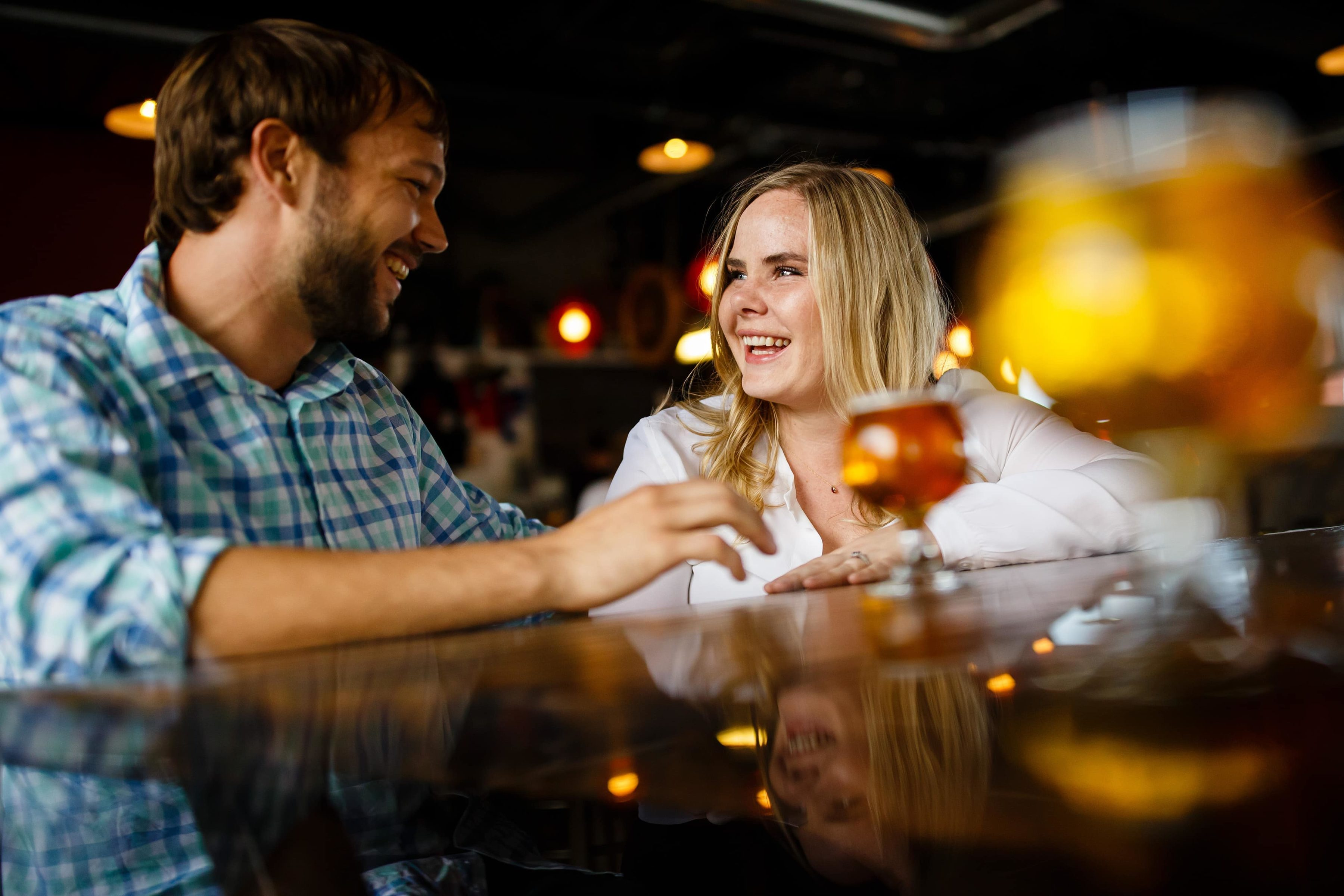 Coza and Joel engoy a beer at Cannonball Creek Brewing Company during their fall Golden engagement