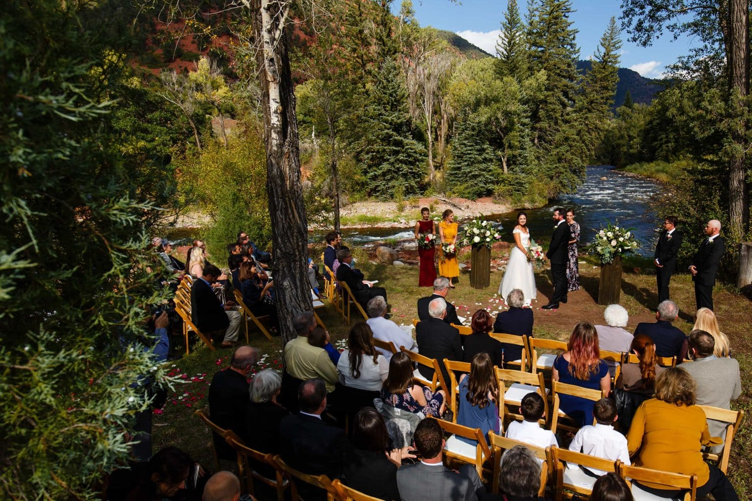 The couple looks out to guests as the creek rushes in the background during their fall wedding ceremony at Snowmass Cottages in Colorado