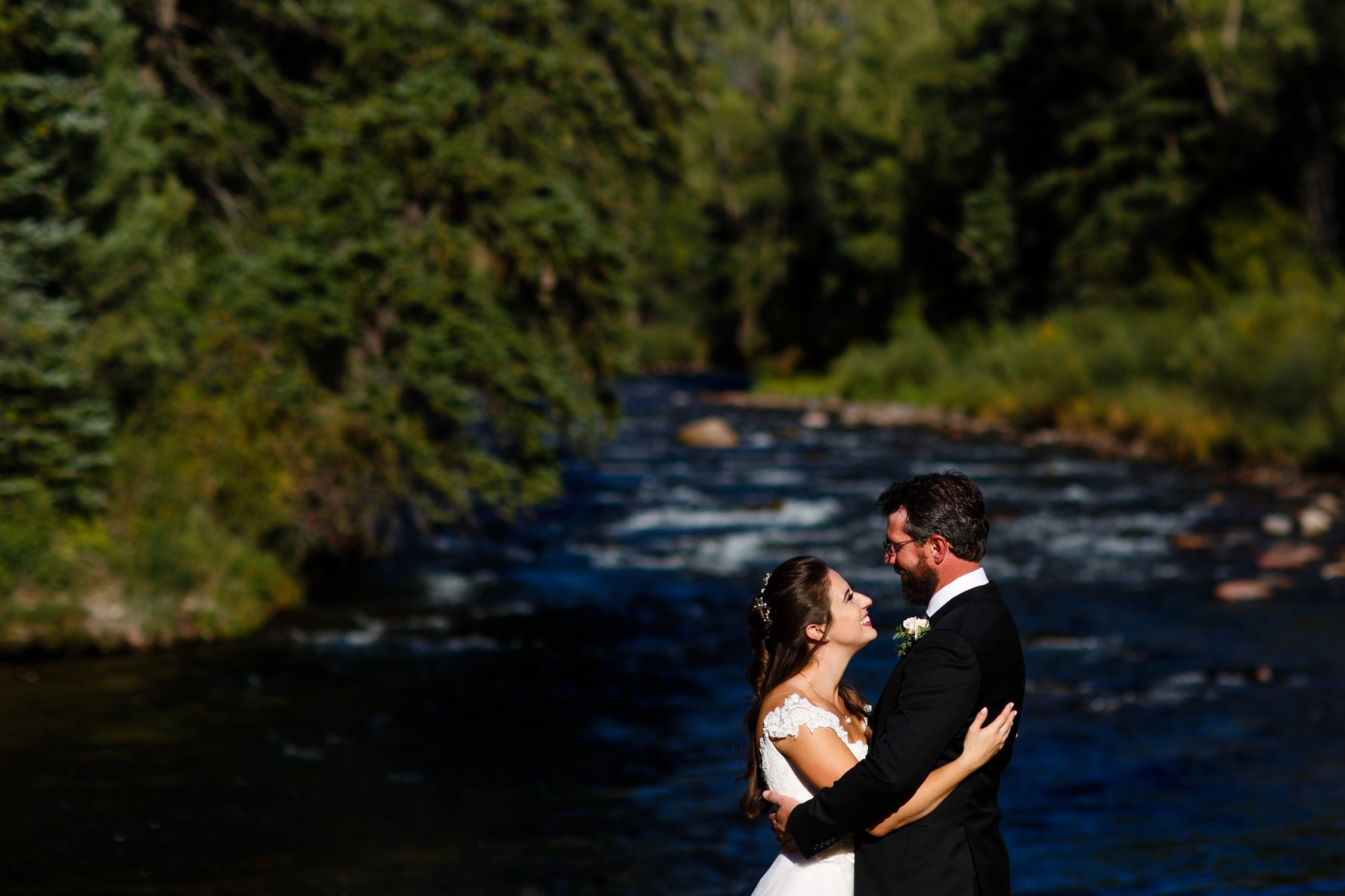 Mallory and Daniel embrace in front of the river at Snowmass Cottages during their wedding