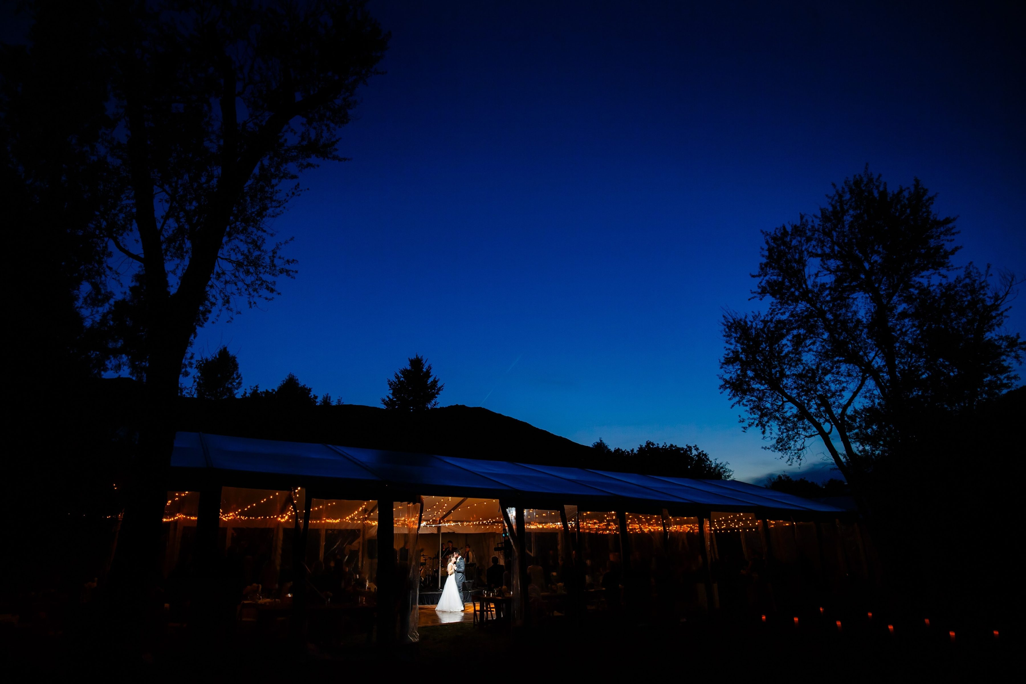 Under a clear sky the couple share their first dance together inside the tent during the reception for their Snowmass Cottages wedding