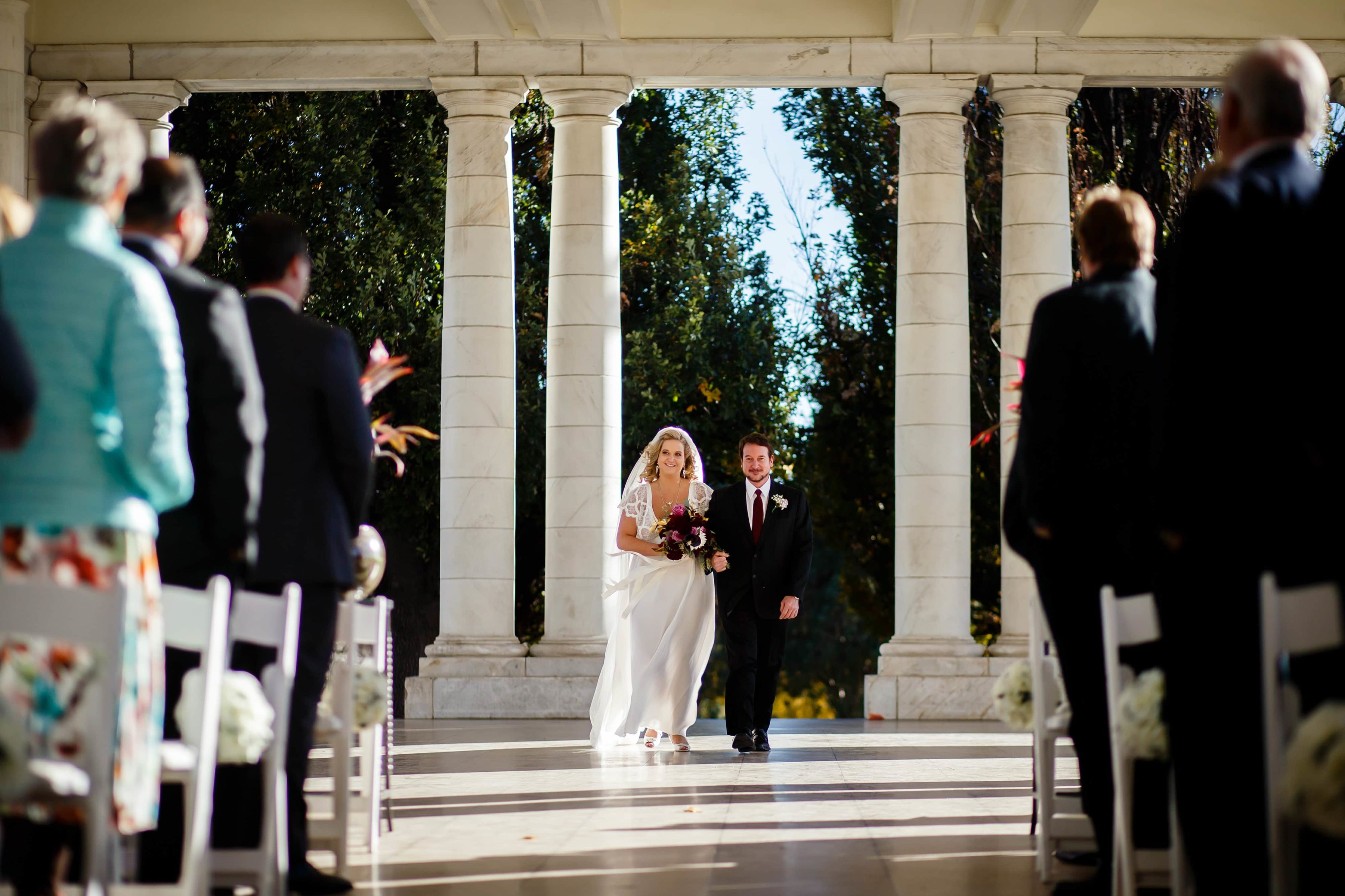 Sarah walks down the aisle with her father during her wedding at the pavillion at Cheesman Park in Denver