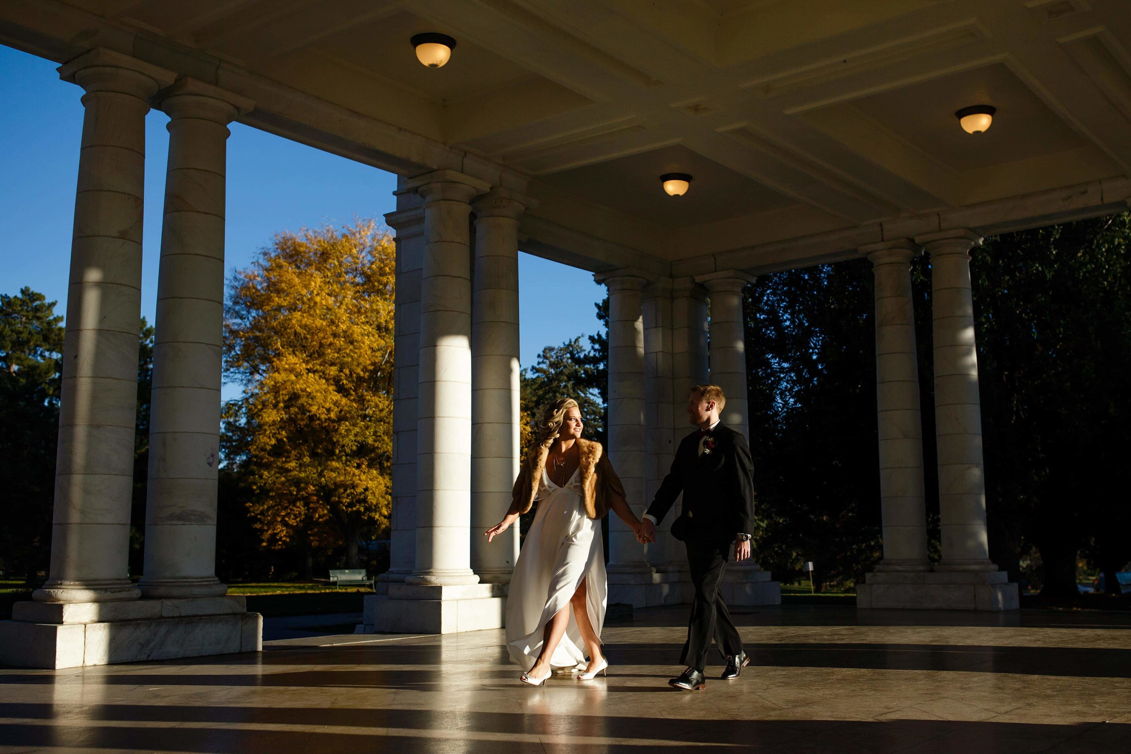 The couple walk together in the Cheesman Park pavillion after their fall wedding in Denver