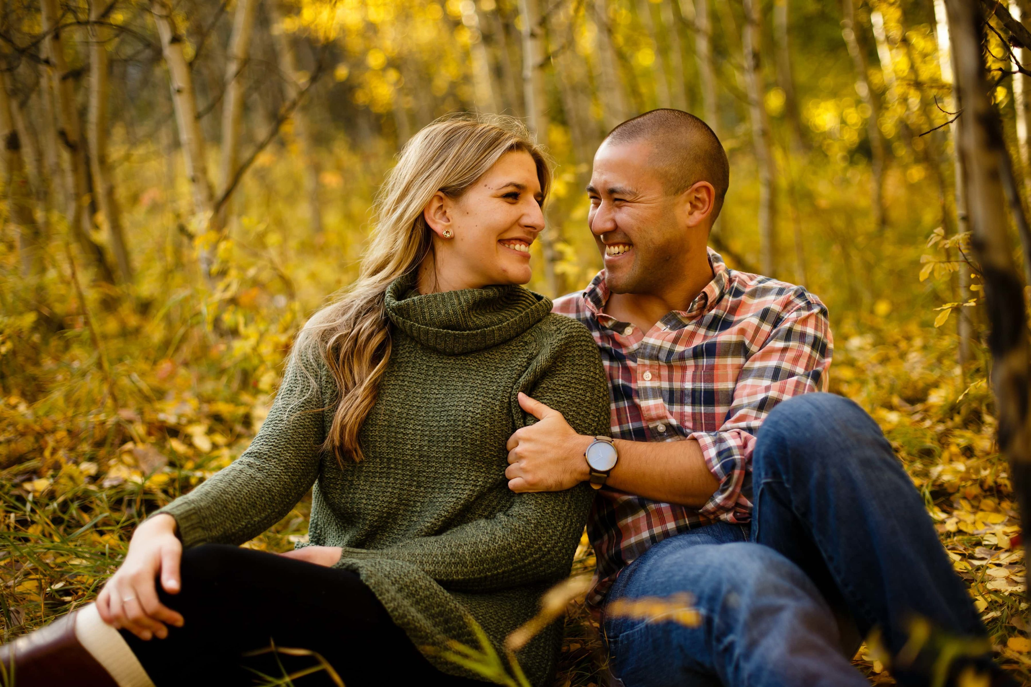 Paige and Adam sit in a grove of fall color during their engagement session outside of Golden Colorado