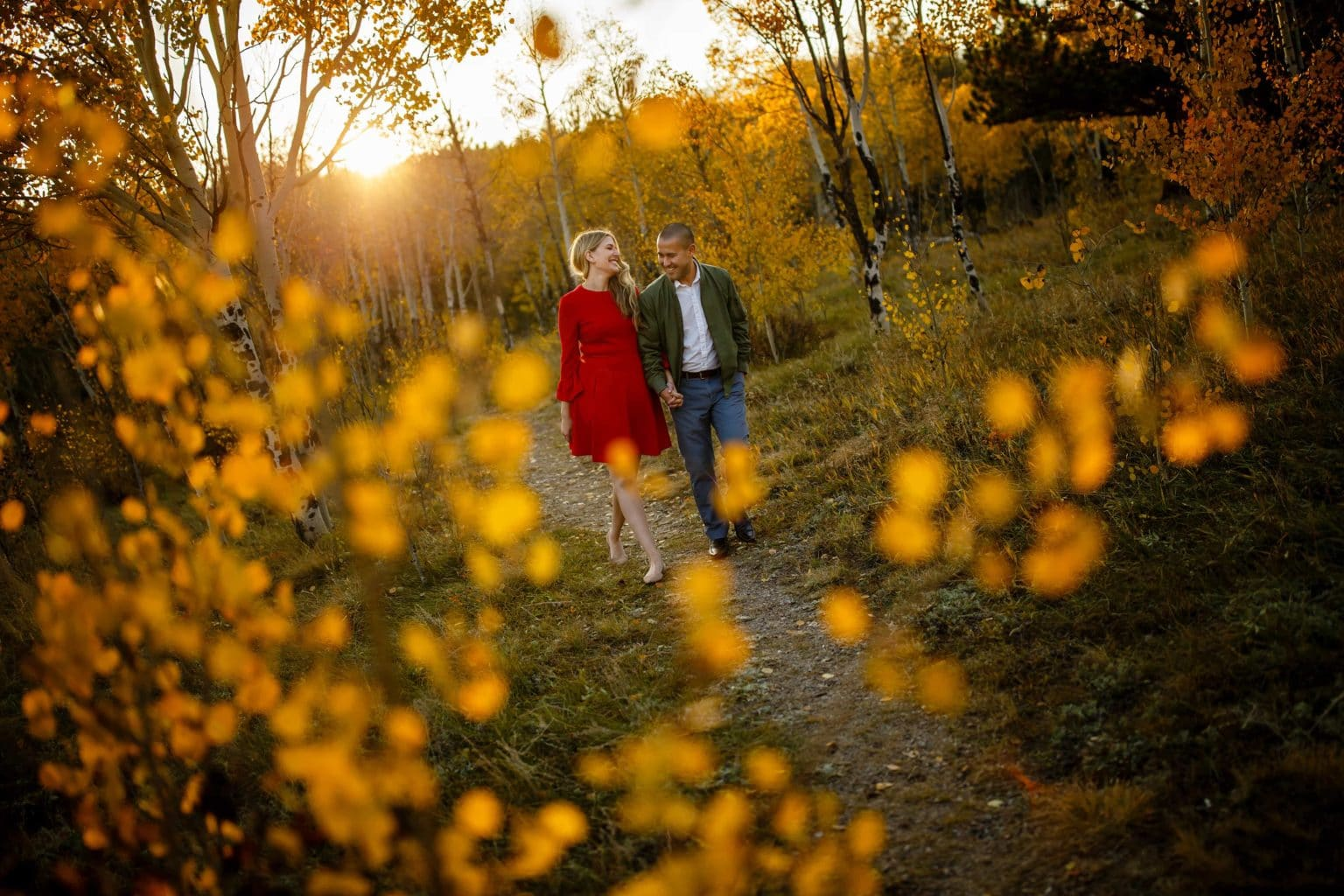 Paige and Adam walk along Mule Deer Trail during their Golden Gate Canyon State Park engagement