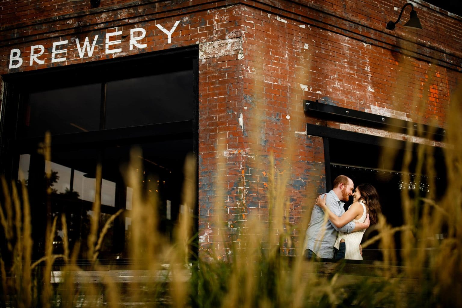 Chris and Angie embrace outside of Briar Common Brewery in the Jefferson Park neighborhood of Denver during their engagement photos