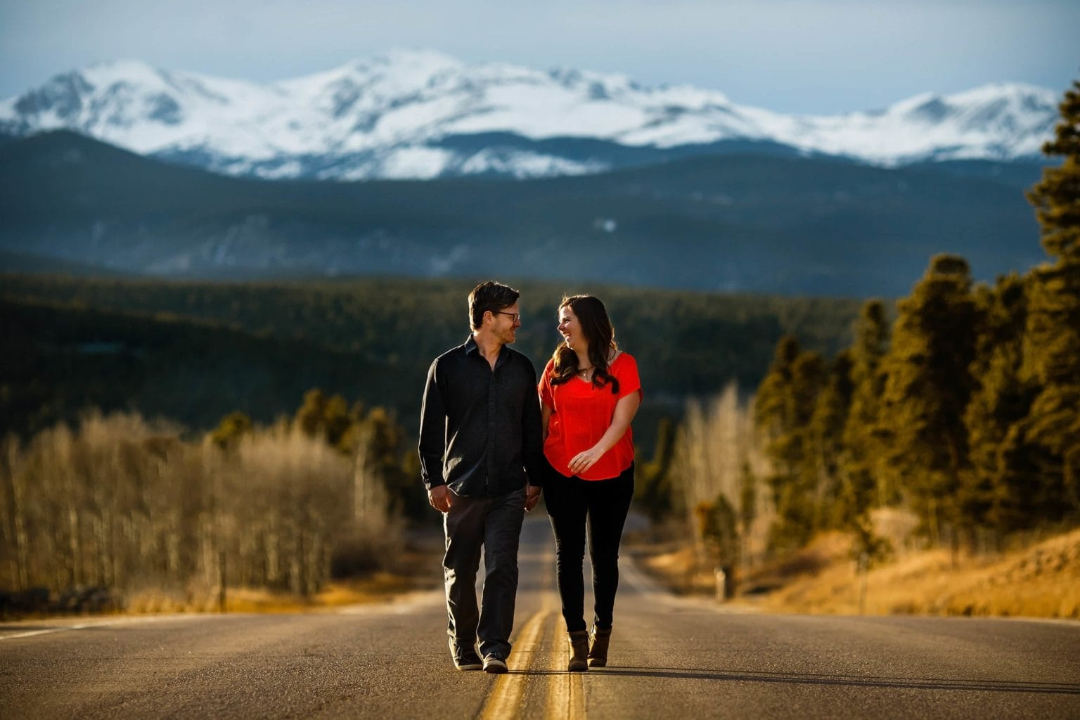 Brian and Kate hold hands and walk along Colorado highway 119 in Black Hawk, Colorado with the snow capped mountains seen in the background during their Spring Golden Gate Canyon State Park engagement