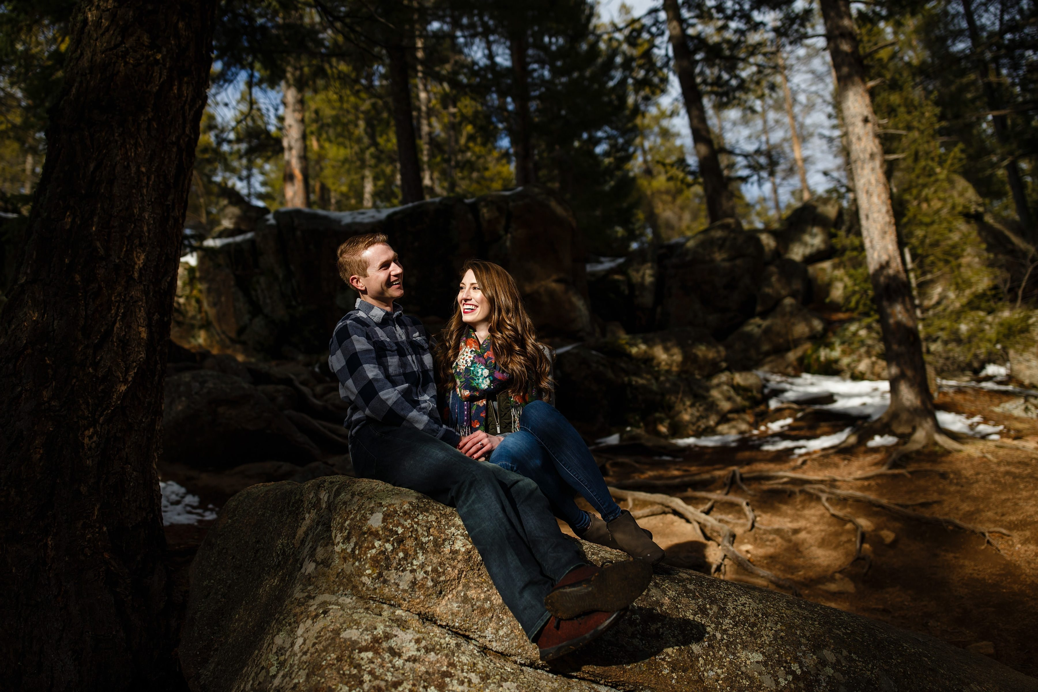 A couple shares a laugh at Maxwell Falls during their Evergreen engagement session