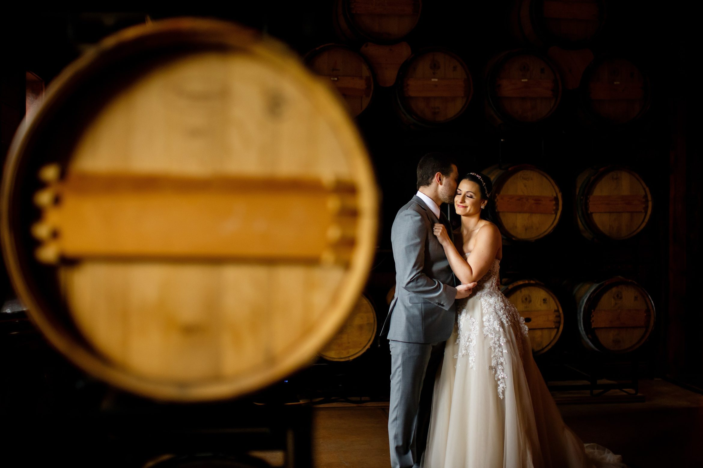 Jordan kisses Danielle on the cheek in the barrell room at Crooked Willow Farms in Larkspur, Colorado