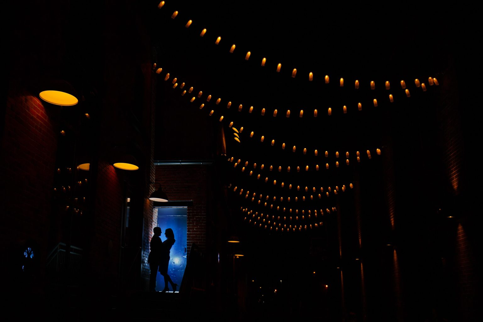 Joel and Katie share a moment together at The Dairy Block at night in downtown Denver during their spring engagement photos