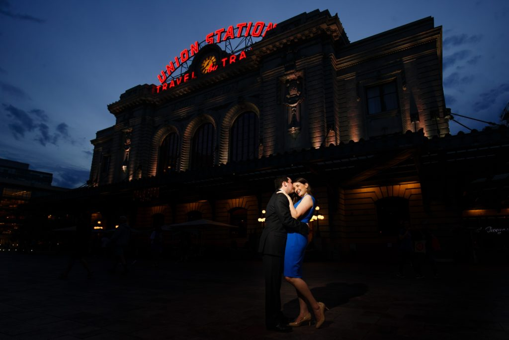 Joel kisses Katie in front of Denver's Union Station during their spring engagement session at twilight