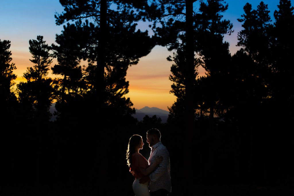 Sharon and Nick embrace as the sun sets over the mountains during their colorful engagement in Golden Gate Canyon State Park