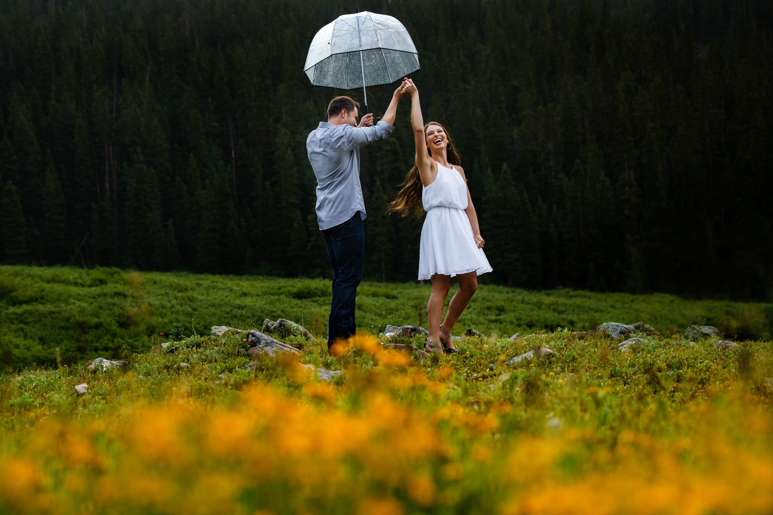 A couple dances in the rain near a patch of wildflowers during their Loveland Pass summer engagement session in Colorado
