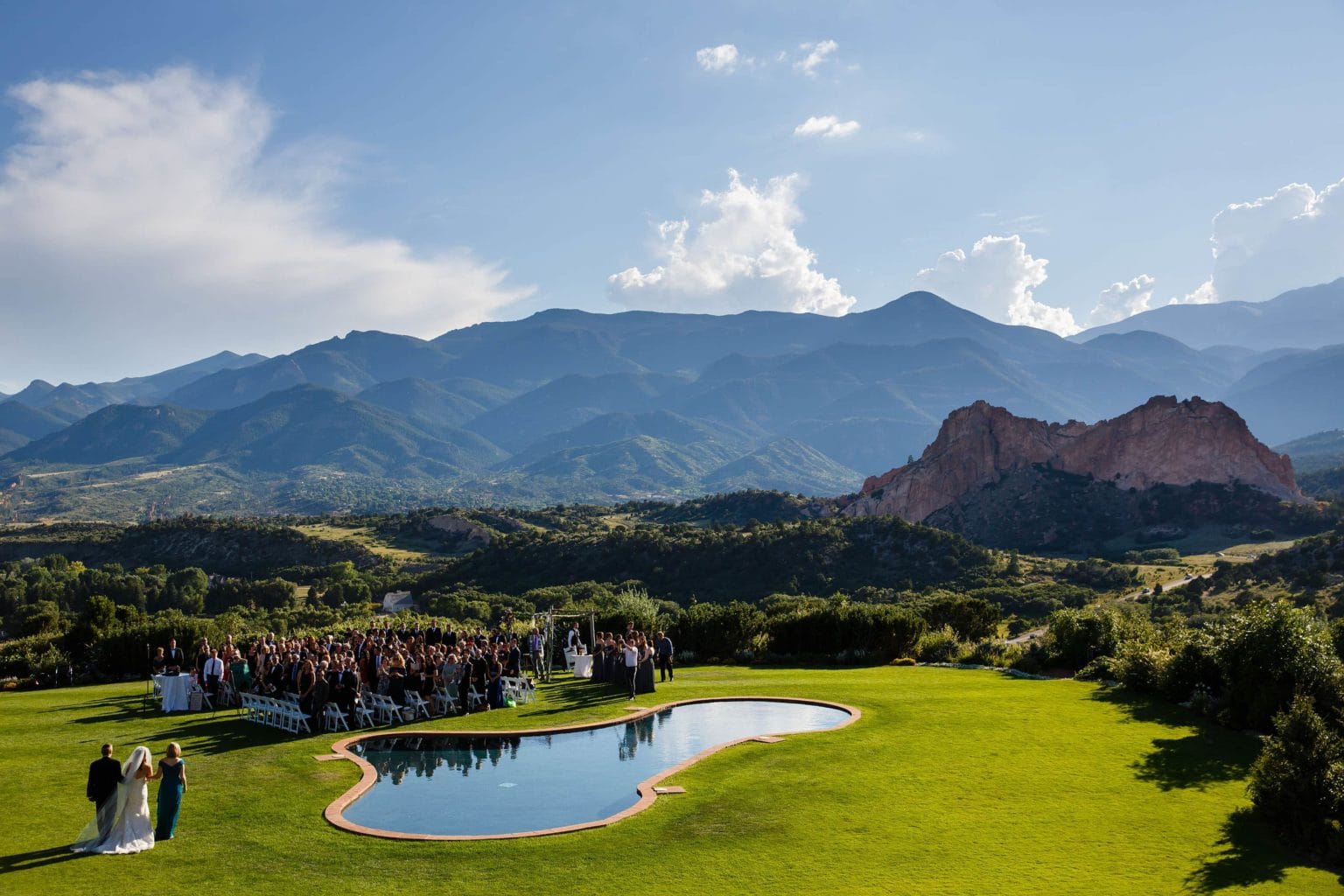 A bride walks down the aisle during her wedding at Garden of the Gods Club in Colorado Springs