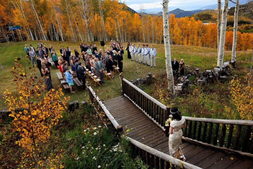 A bride walks out of Lynn Britt cabin during her wedding in Snowmass Colorado