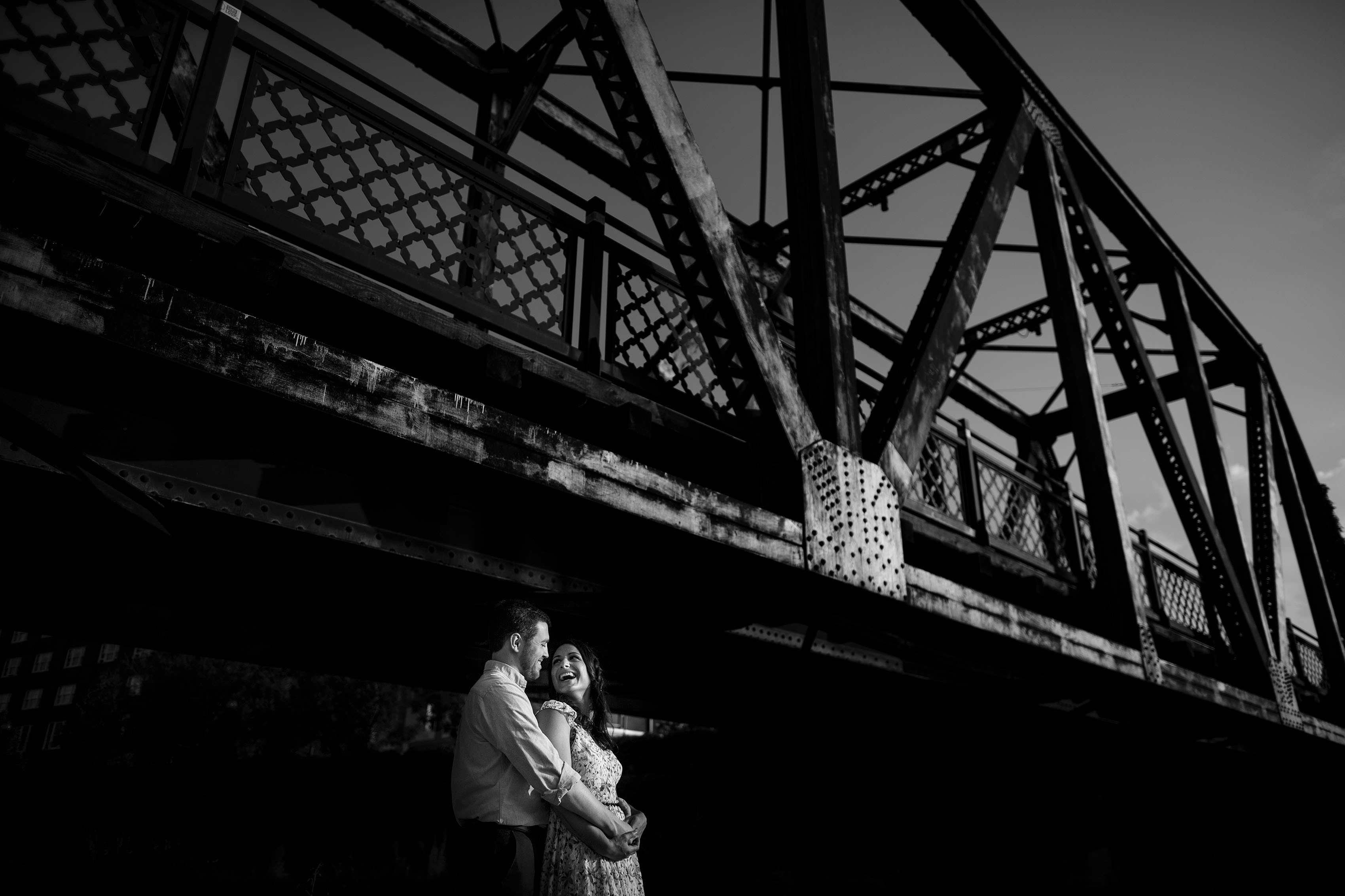 A couple embraces under the Wynkoop bridge during their LoDo Denver engagement photos