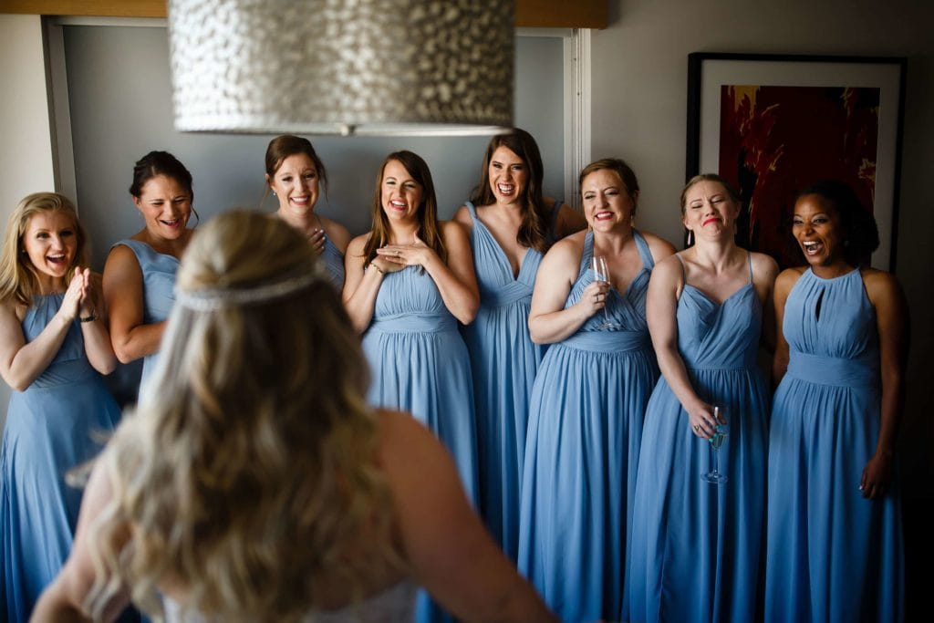 Bridesmaids react to seeing the bride in her dress at the Art Hotel in Denver