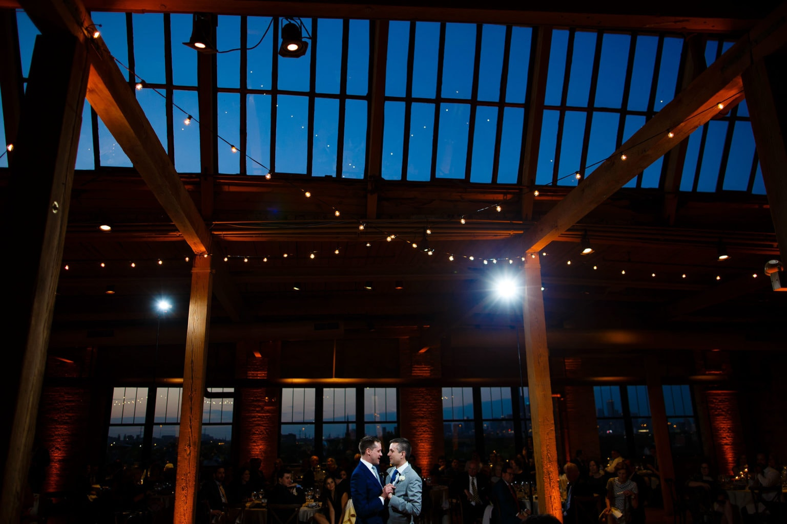The grooms share a first dance during twilight at their Bridgeport Art Center wedding in Chicago