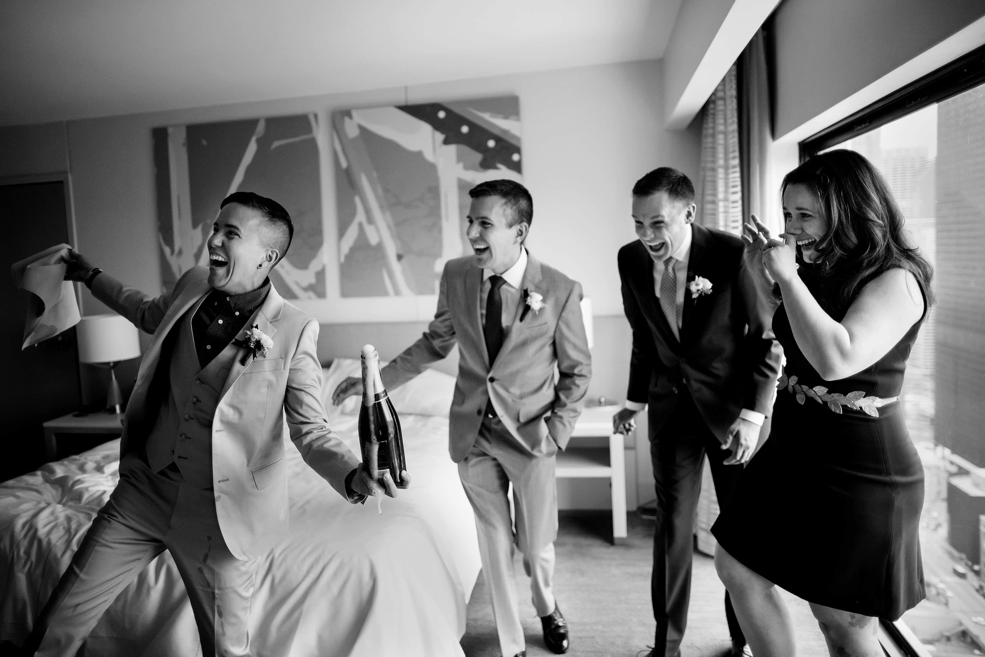 Wedding party laugh while opening champagne