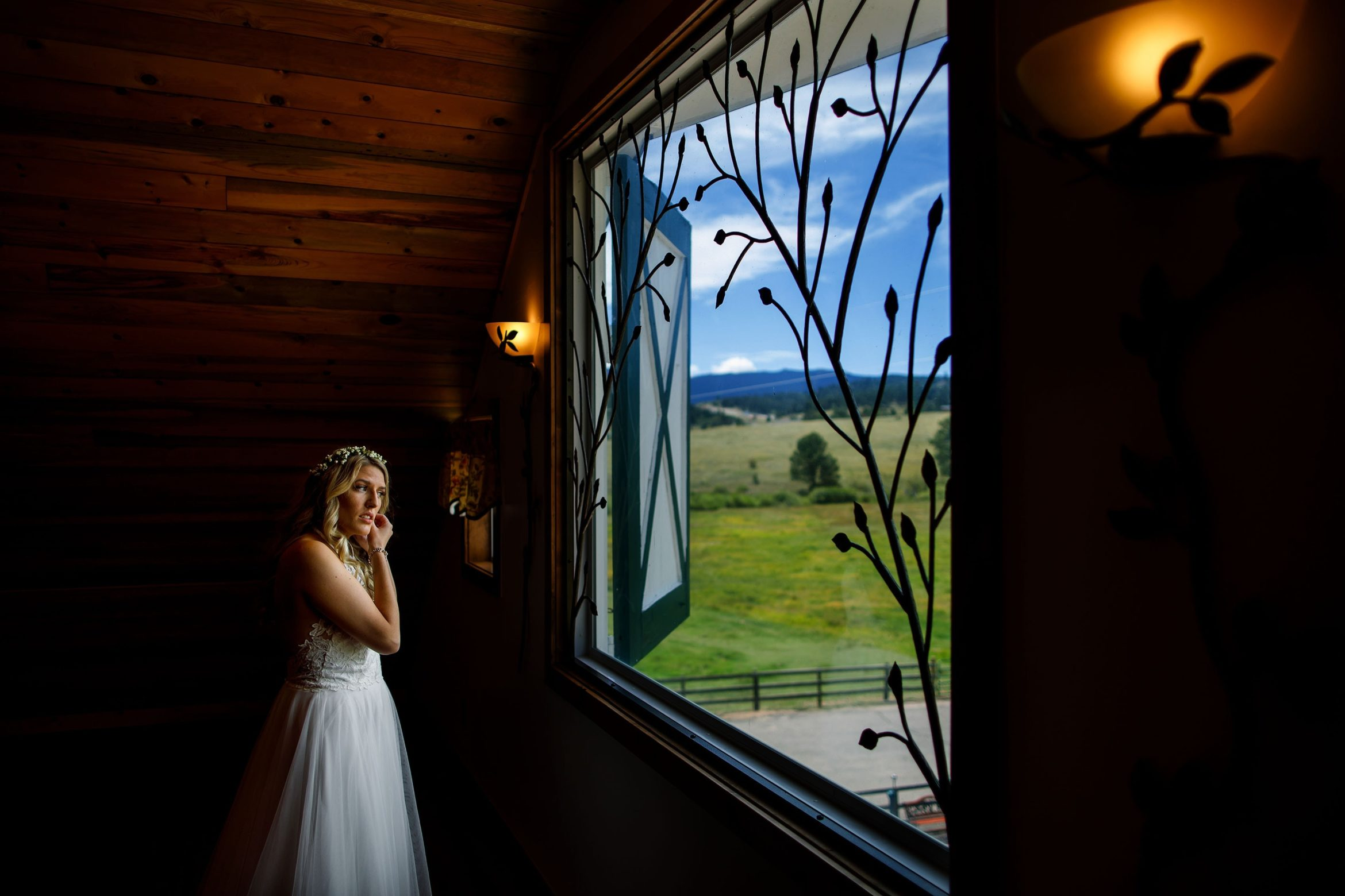 Paige puts on her ear ring before her summer barn wedding at Deer Creek Valley Ranch