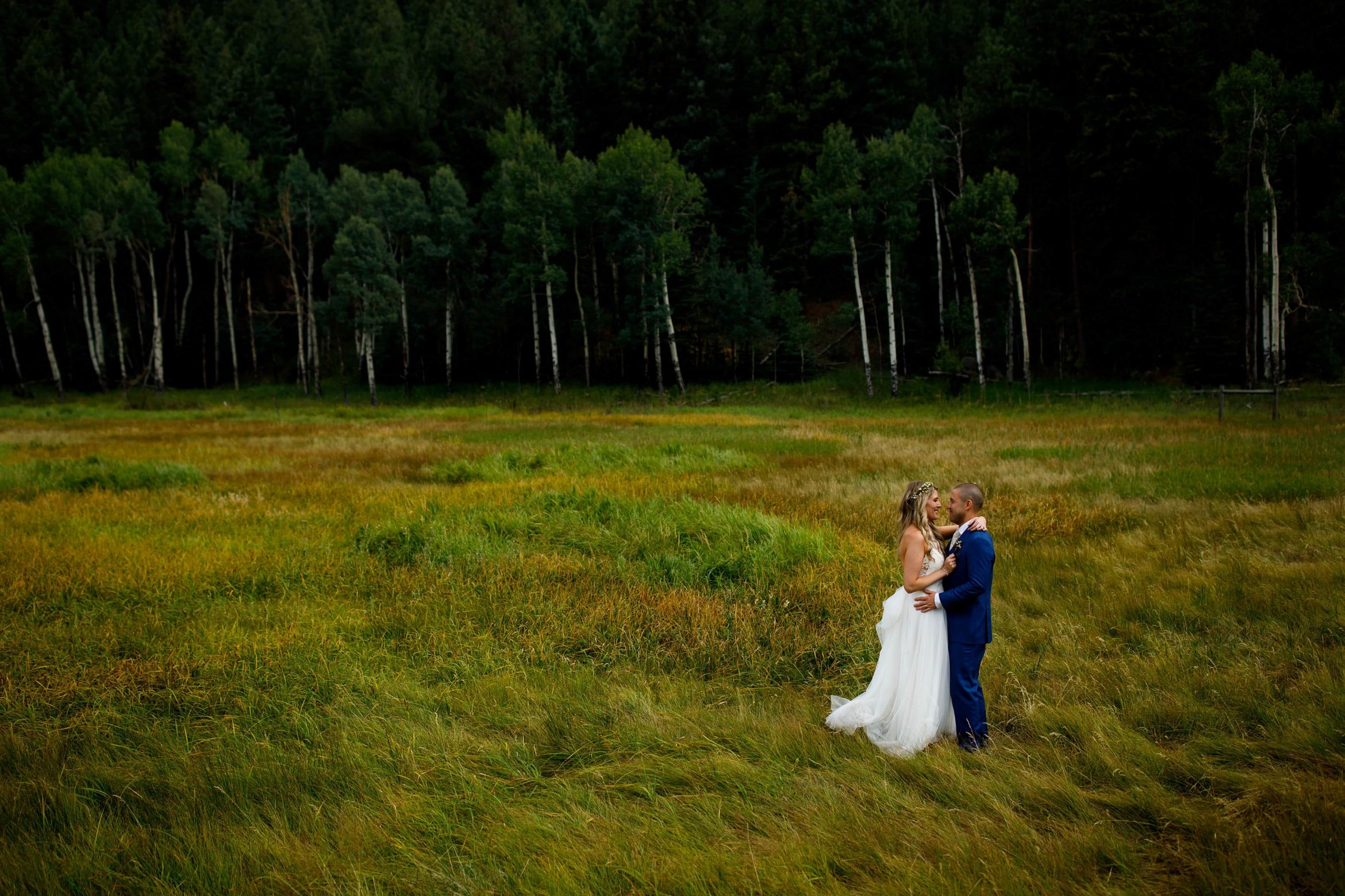 The couple embrace each other in the tall grass at Deer Creek Valley Ranch