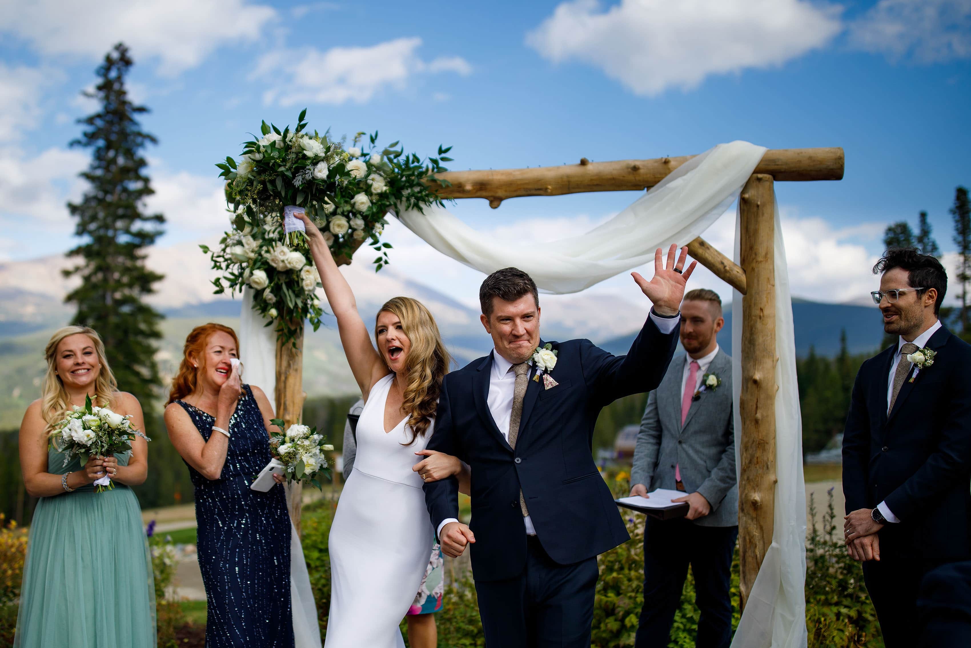 The bride and groom celebrate in front of a wooden arch with flowers at TenMile