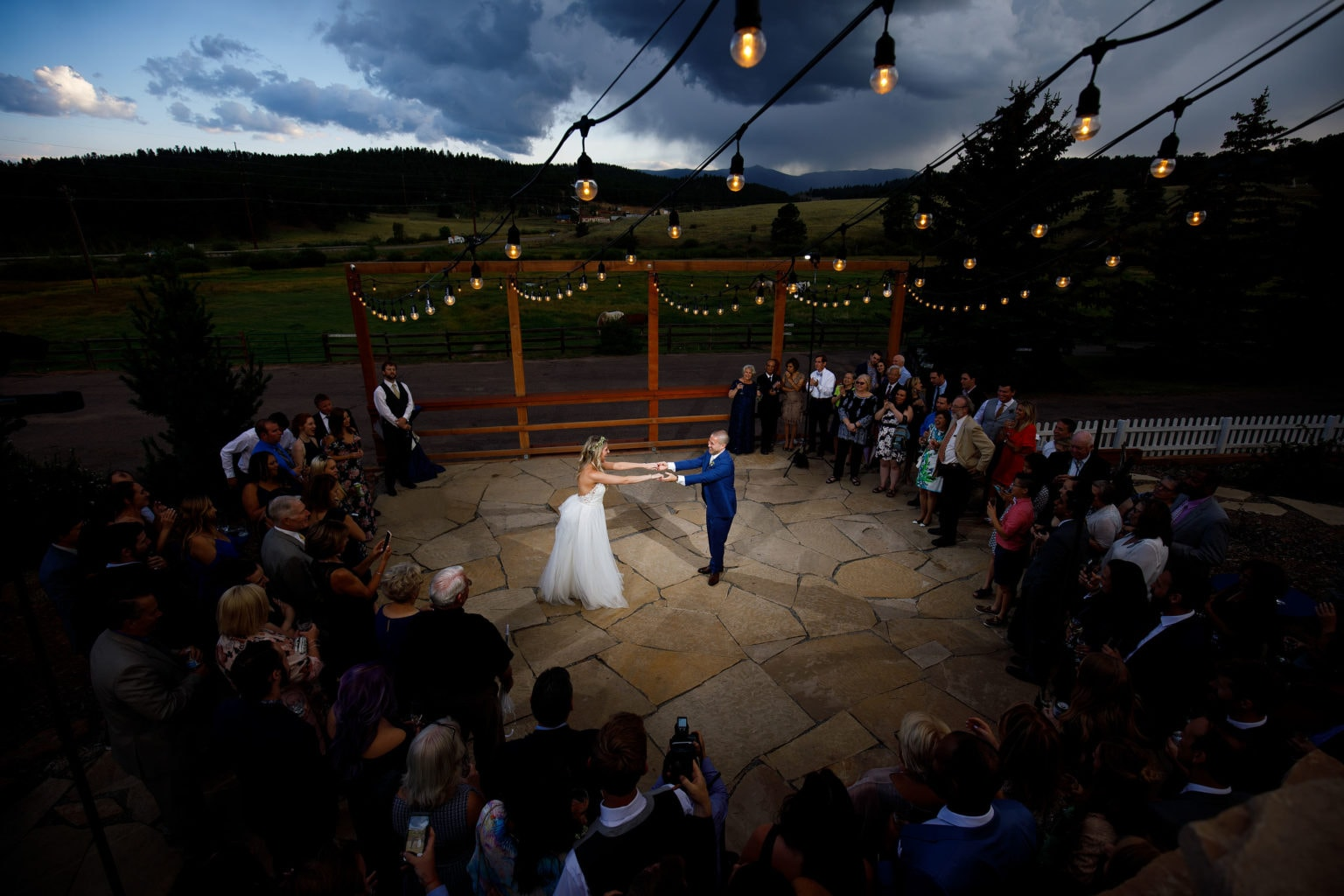 The newlyweds dance on the patio under market lights during their summer barn wedding at Deer Creek Valley Ranch