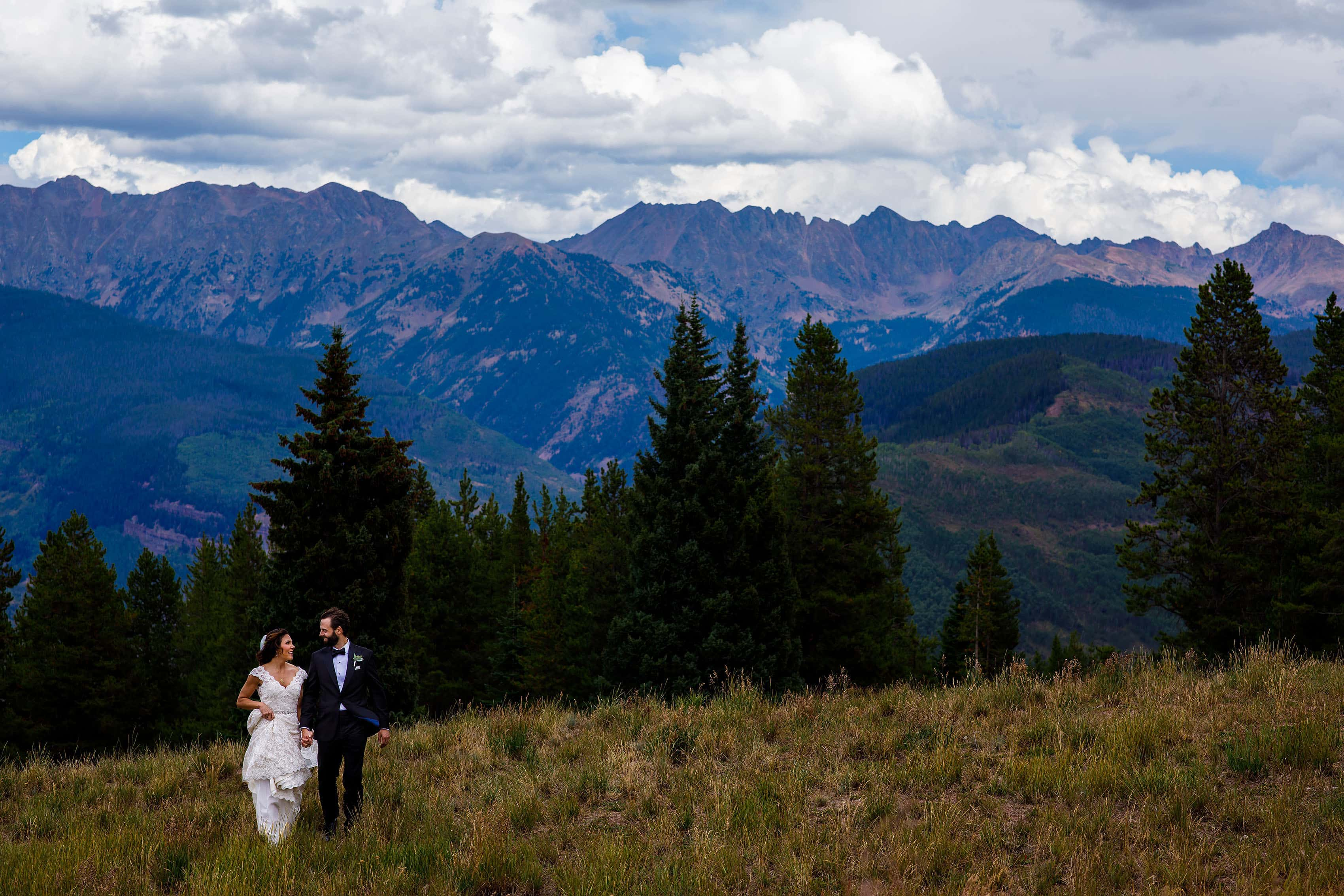 The bride and groom walk together atop Vail mountain on their wedding day