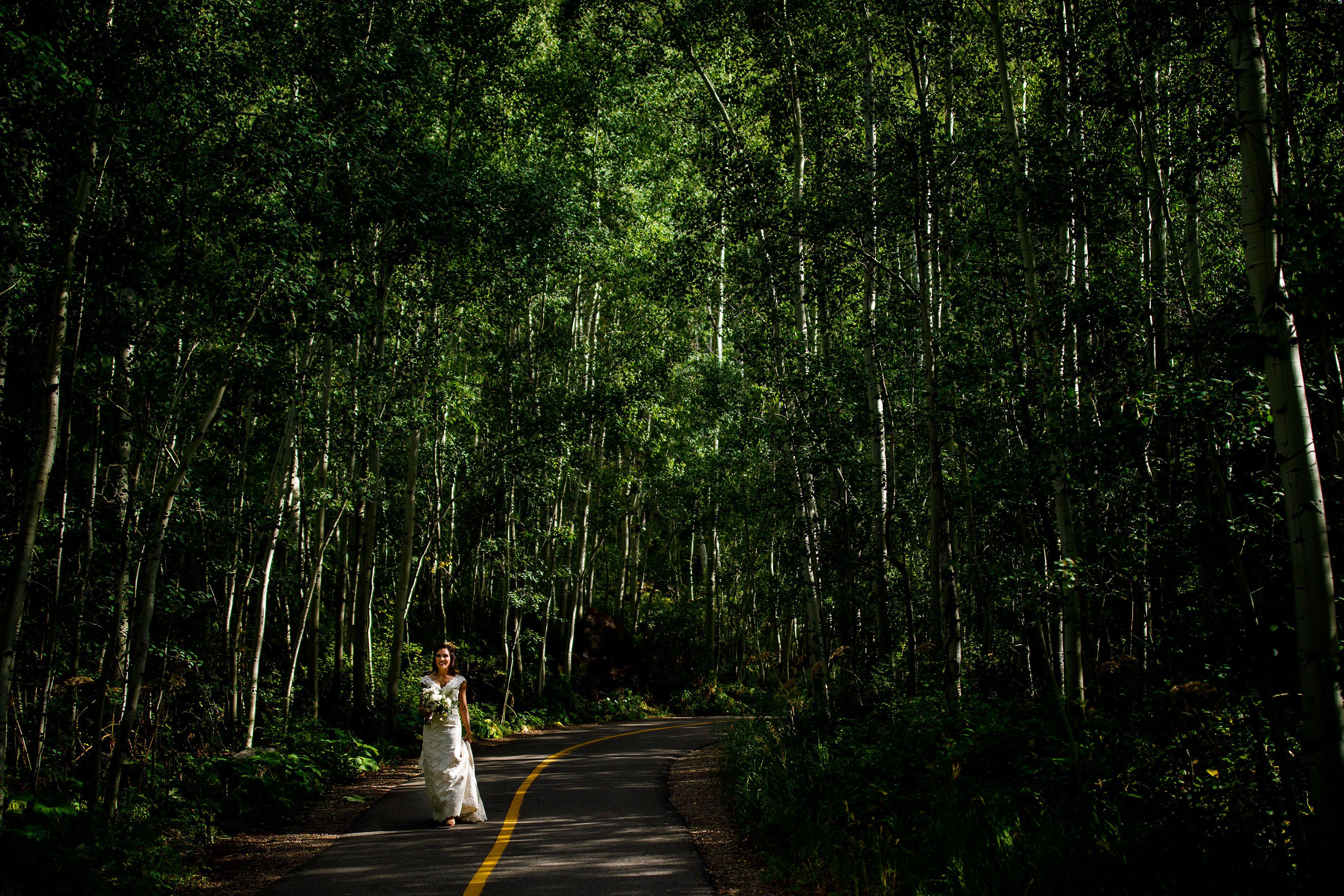 A bride walks through the aspens before her Vail Golf Club wedding