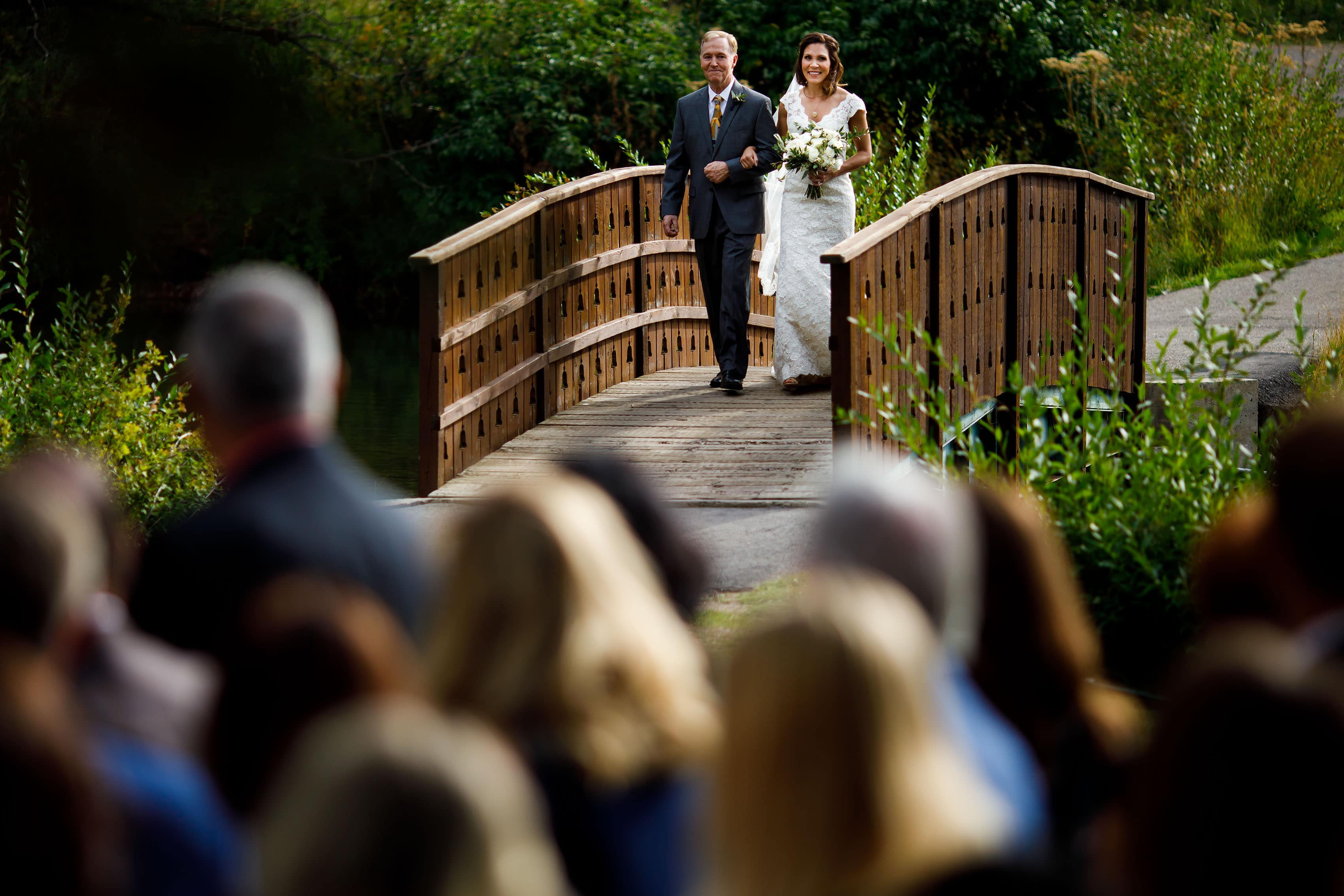 Christine walks with her father across the bride during her Vail Golf Club wedding