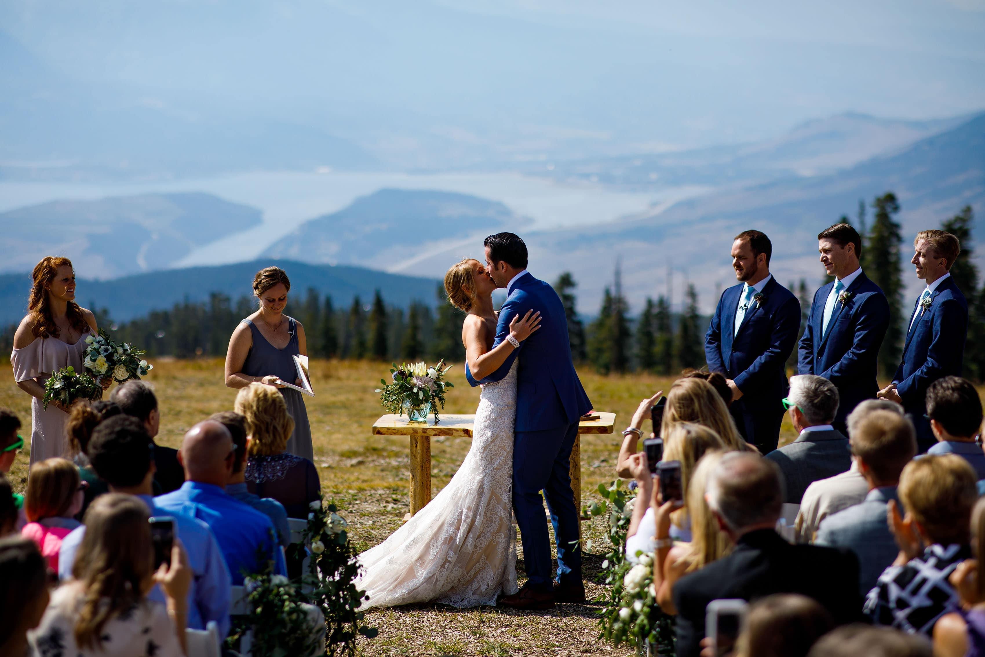 A couple share their first kiss during their Keystone wedding ceremony on Dercum Mountain Schoolmarm run