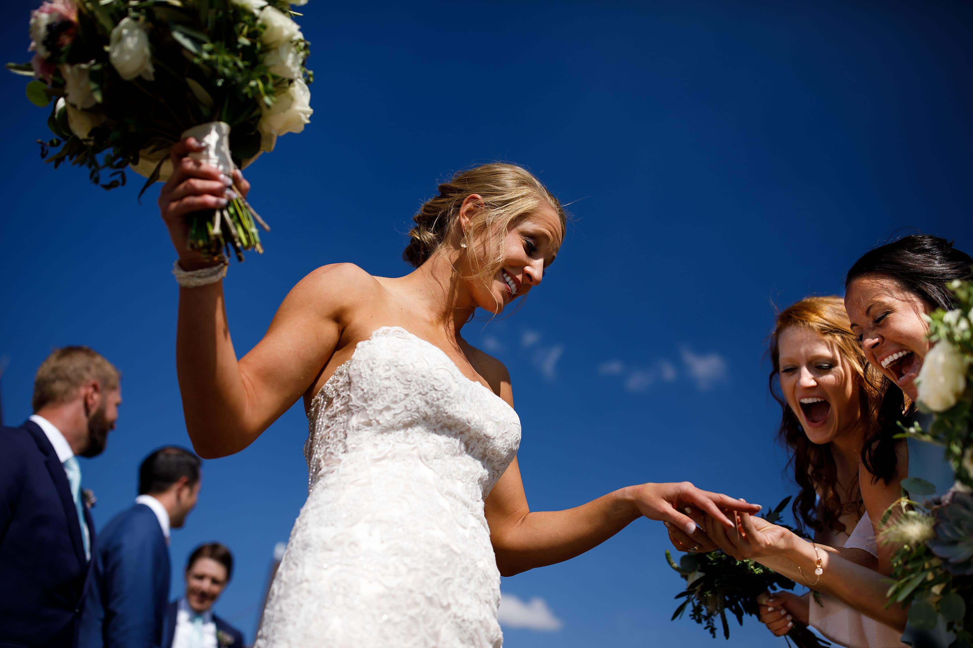 A bride shows off her ring after her Keystone wedding ceremony atop Dercum Mountain on a summer day in August