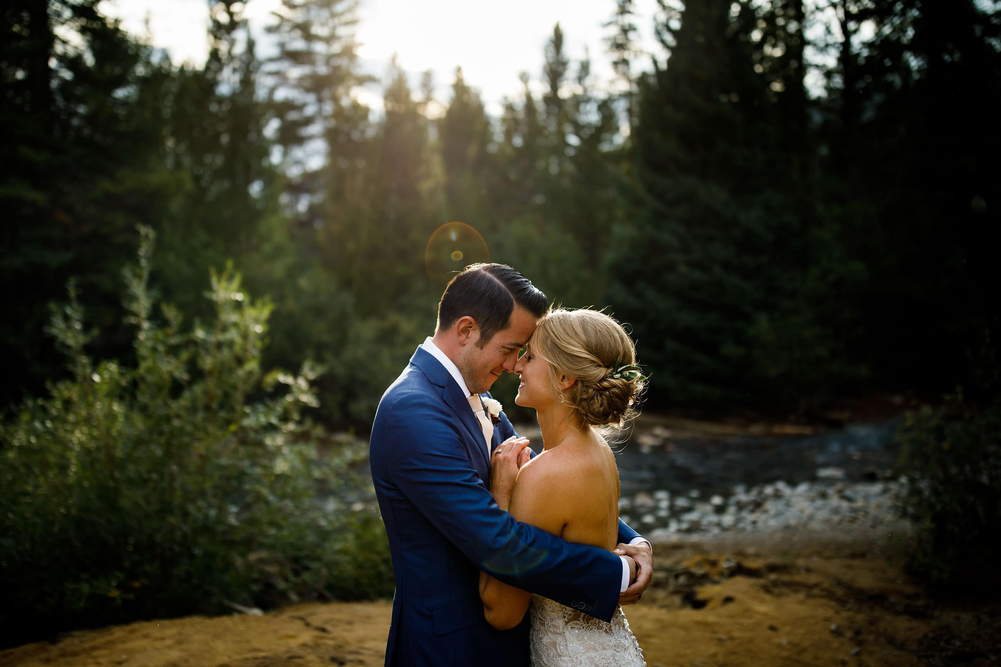 A couple embrace near the Snake River during their summertime Keystone wedding