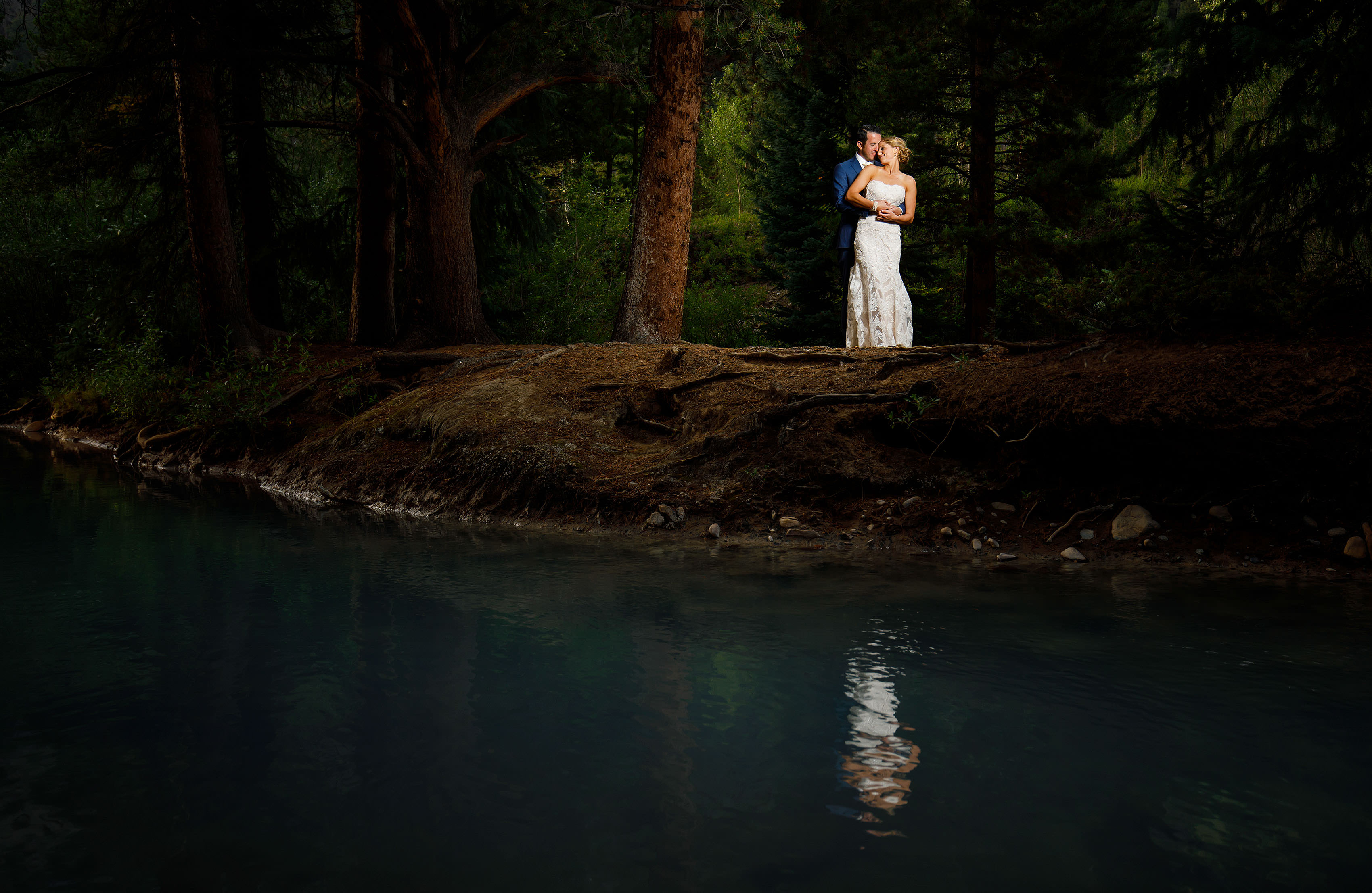 A couple is reflected in the Snake River during their summer Keystone wedding