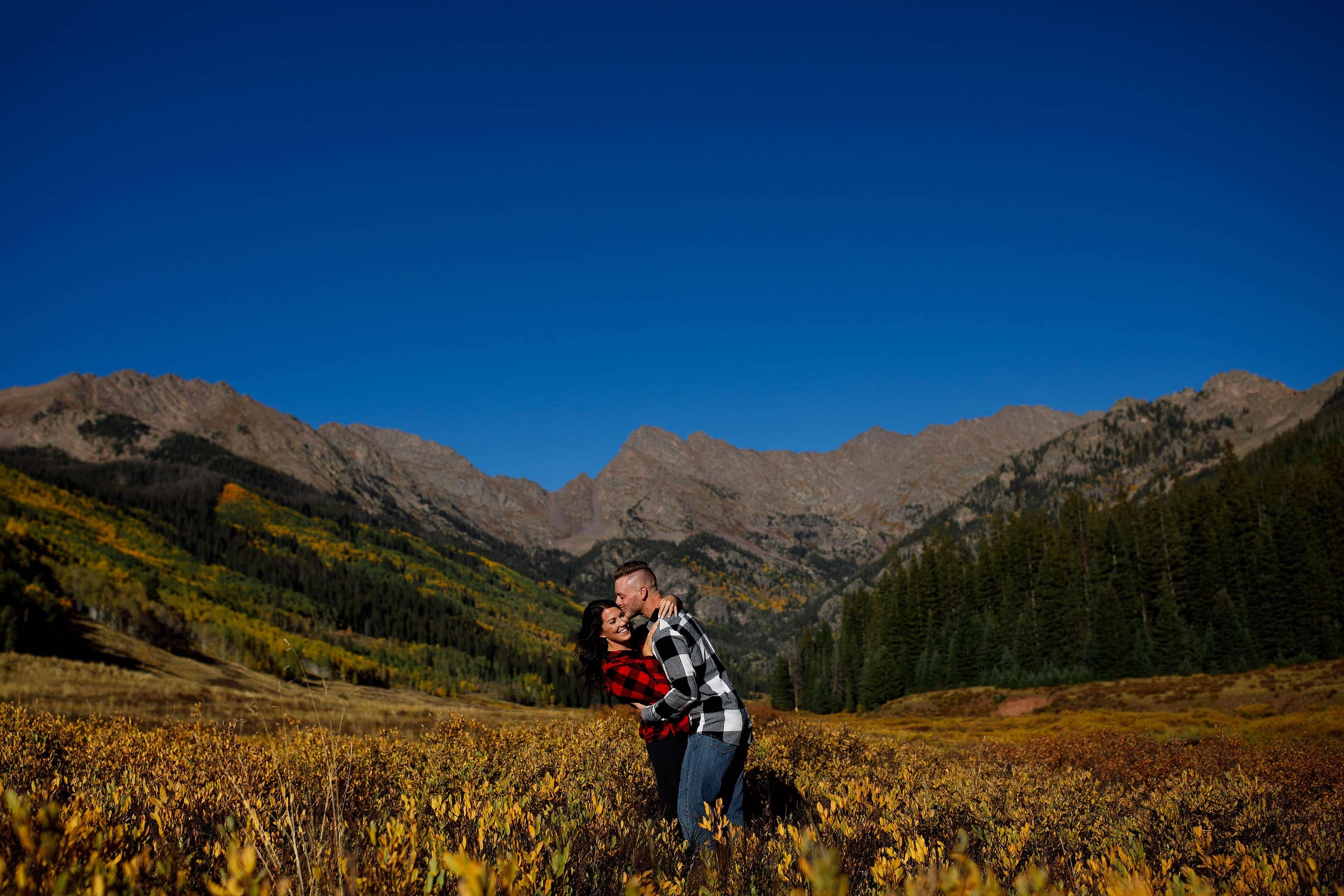 A couple poses in plaid flannel shirts during their fall Piney River Ranch engagement in front of the Gore mountain range near Vail Colorado